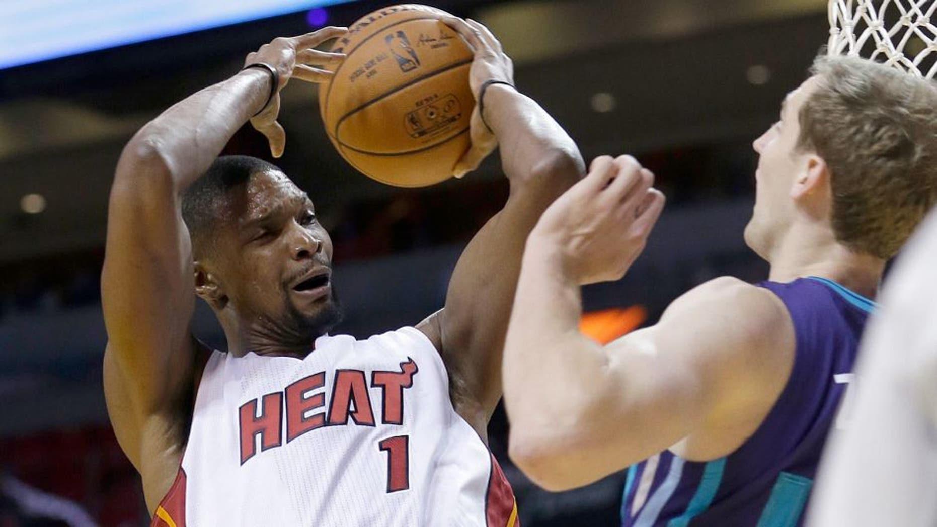 Miami Heat forward Chris Bosh (1) is fouled by Charlotte Hornets forward Cody Zeller (40) as Bosh goes to the basket in the first half of an NBA preseason basketball game, Sunday, Oct. 4, 2015, in Miami. (AP Photo/Alan Diaz)