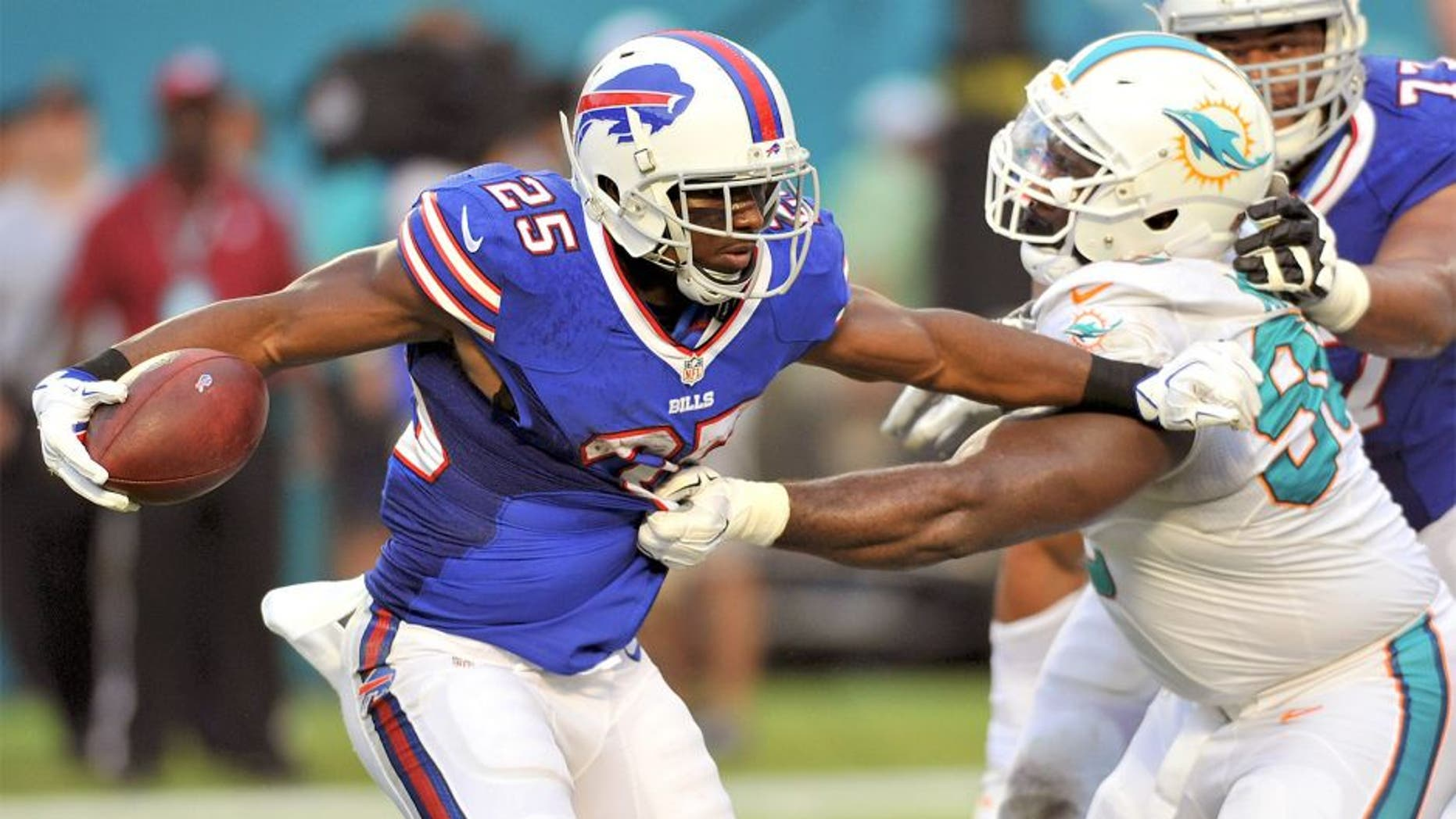 Sep 27, 2015; Miami Gardens, FL, USA; Buffalo Bills running back LeSean McCoy (25) is tackled by Miami Dolphins defensive tackle Earl Mitchell (90) during the first half at Sun Life Stadium. Mandatory Credit: Steve Mitchell-USA TODAY Sports