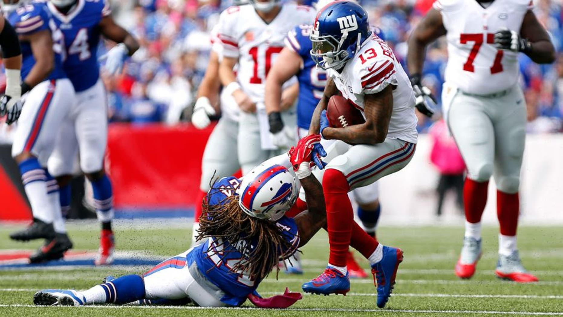 Oct 4, 2015; Orchard Park, NY, USA; New York Giants wide receiver Odell Beckham (13) runs after a catch and is tackled by Buffalo Bills cornerback Stephon Gilmore (24) during the first quarter at Ralph Wilson Stadium. Mandatory Credit: Kevin Hoffman-USA TODAY Sports