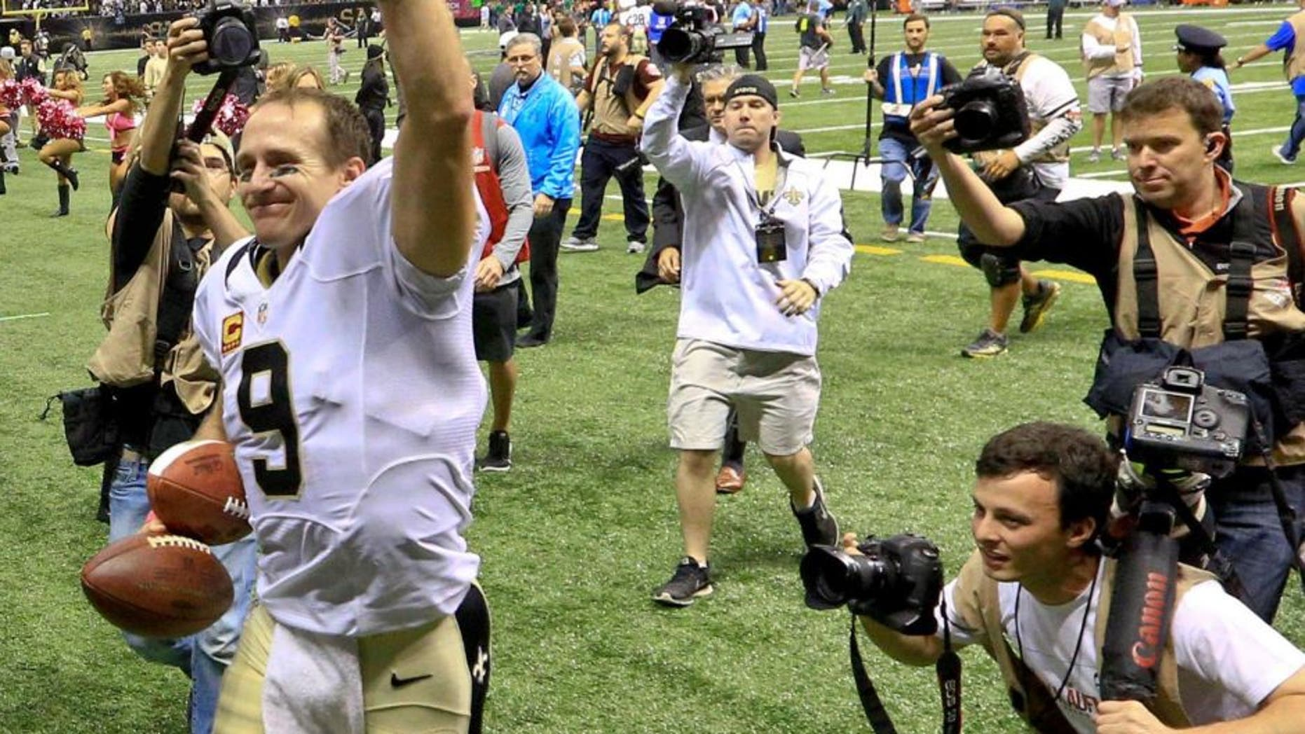 Oct 4, 2015; New Orleans, LA, USA; New Orleans Saints quarterback Drew Brees (9) walks off the field after a 80 yard game winning touchdown pass to running back C.J. Spiller (not pictured) during overtime against the Dallas Cowboys at the Mercedes-Benz Superdome. The Saints won 26-20. The touchdown pass by Brees was the 400th touchdown pass of his career. Mandatory Credit: Derick E. Hingle-USA TODAY Sports