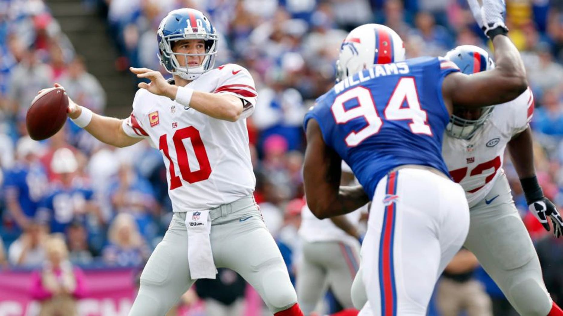 Oct 4, 2015; Orchard Park, NY, USA; New York Giants quarterback Eli Manning (10) throws a pass under pressure by Buffalo Bills defensive end Mario Williams (94) during the second half at Ralph Wilson Stadium. Giants beat the Bills 24-10. Mandatory Credit: Kevin Hoffman-USA TODAY Sports