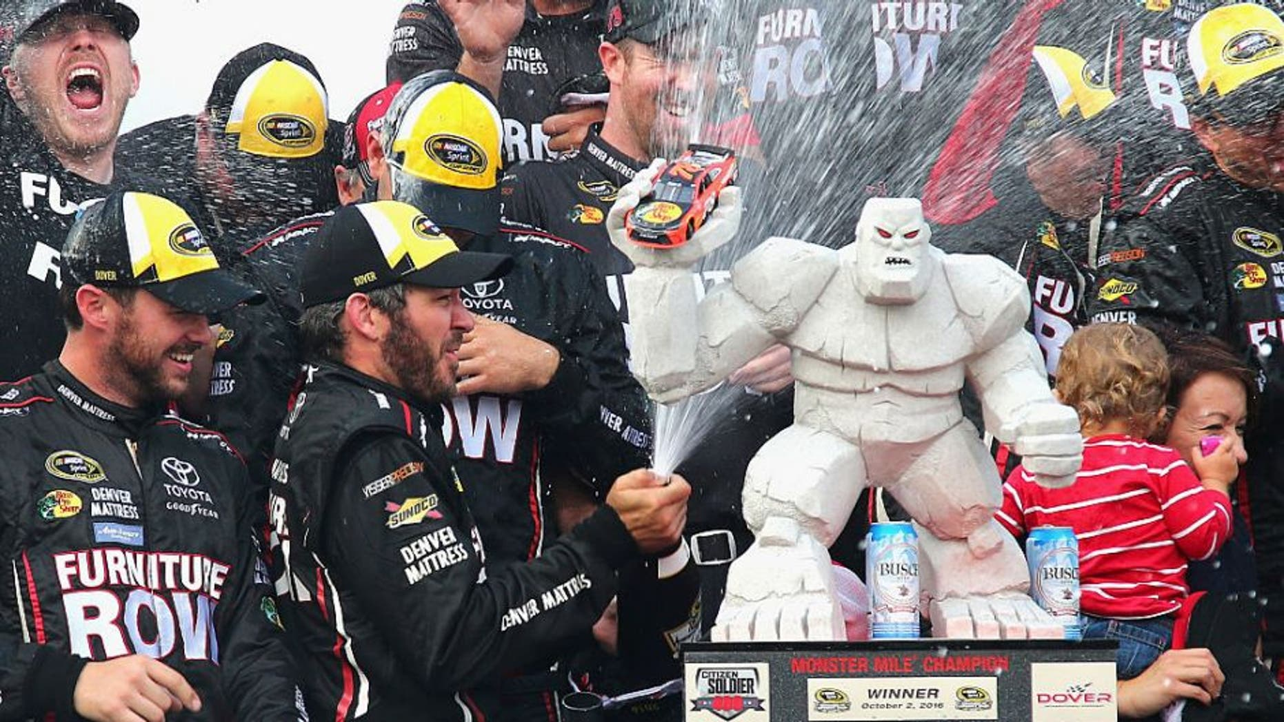 DOVER, DE - OCTOBER 02: Martin Truex Jr., driver of the #78 Furniture Row/Denver Mattress Toyota, celebrates with the trophy in Victory Lane after winning the NASCAR Sprint Cup Series Citizen Solider 400 at Dover International Speedway on October 2, 2016 in Dover, Delaware. (Photo by Sarah Crabill/NASCAR via Getty Images)