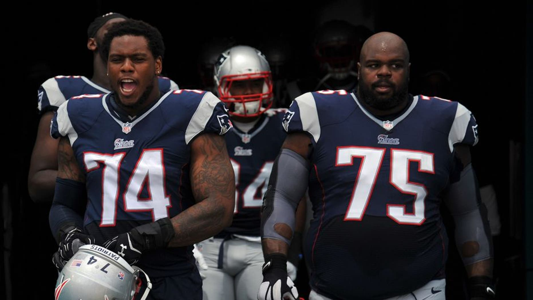 Sep 7, 2014; Miami Gardens, FL, USA; New England Patriots defensive tackle Dominique Easley (left) and defensive tackle Vince Wilfork (right) both take the field before a game against the Miami Dolphins at Sun Life Stadium. Mandatory Credit: Steve Mitchell-USA TODAY Sports