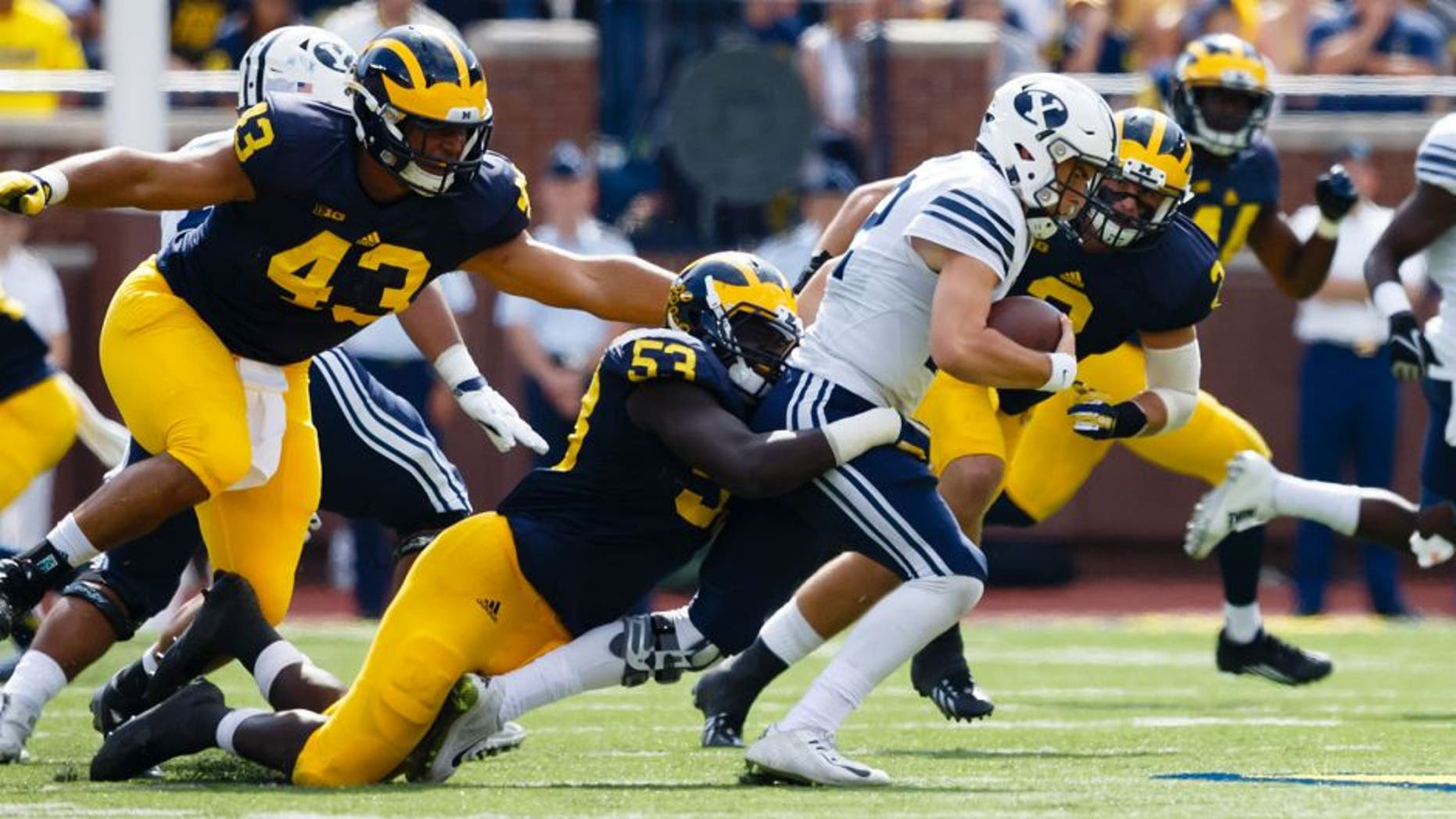 Sep 26, 2015; Ann Arbor, MI, USA; Brigham Young Cougars quarterback Tanner Mangum (12) is tackled by Michigan Wolverines defensive end Mario Ojemudia (53) in the third quarter at Michigan Stadium. Michigan won 31-0. Mandatory Credit: Rick Osentoski-USA TODAY Sports