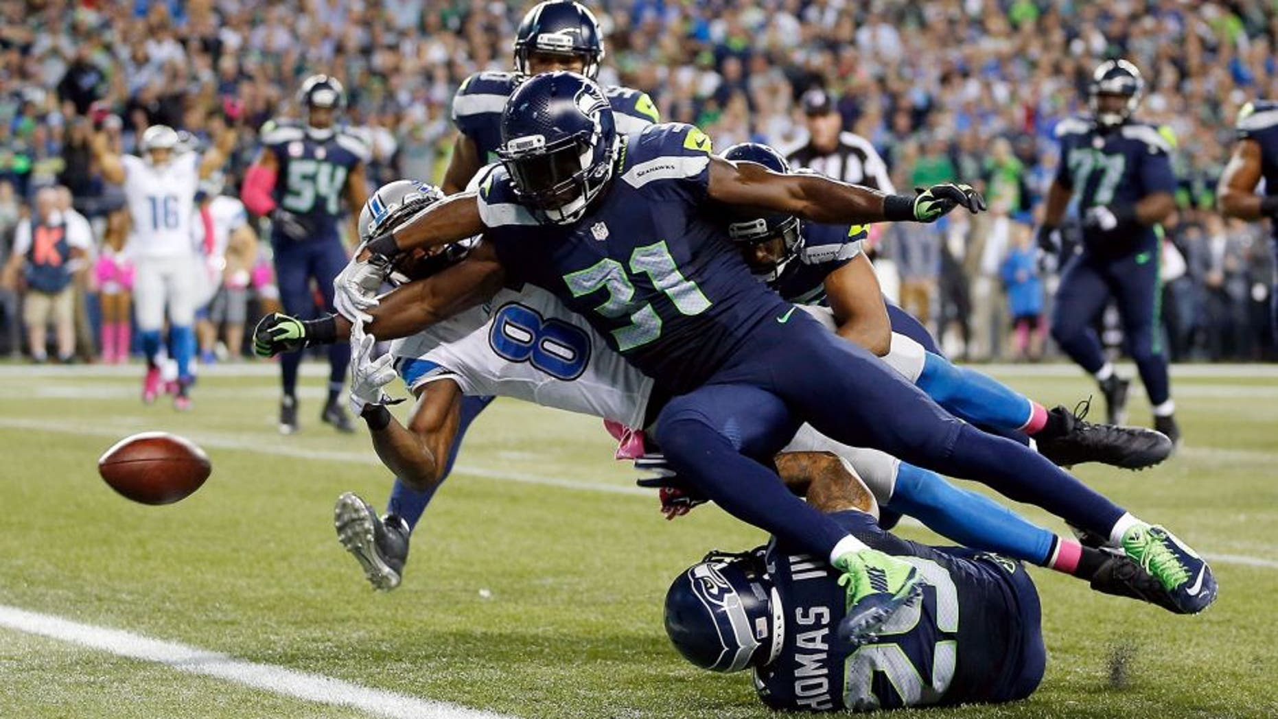 SEATTLE, WA - OCTOBER 05: Kam Chancellor #31 of the Seattle Seahawks forces Calvin Johnson #81 of the Detroit Lions to fumble the ball near the goal line during the fourth quarter of their game at CenturyLink Field on October 5, 2015 in Seattle, Washington. (Photo by Otto Greule Jr/Getty Images)