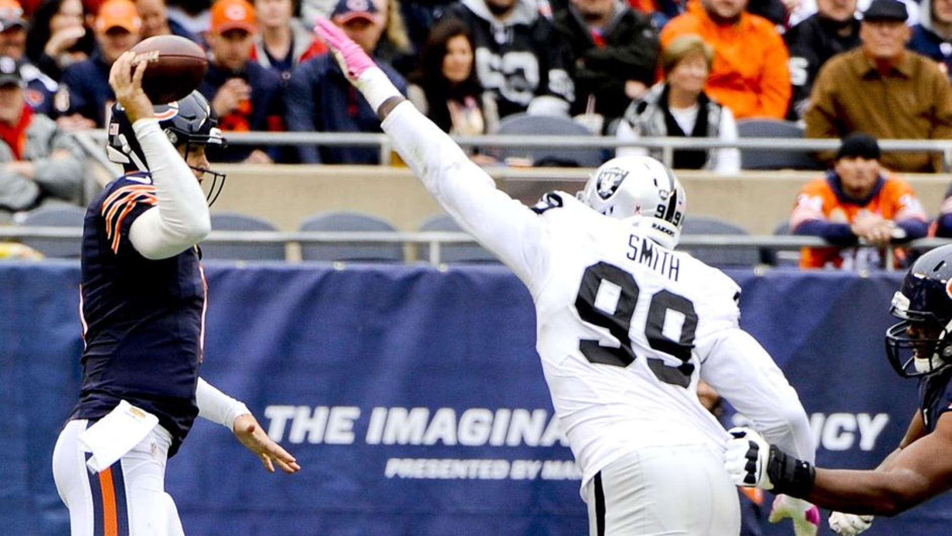 Oct 4, 2015; Chicago, IL, USA; Oakland Raiders outside linebacker Aldon Smith (99) tips the ball after Chicago Bears quarterback Jay Cutler (6) throws in the first quarter at Soldier Field. Mandatory Credit: Matt Marton-USA TODAY Sports