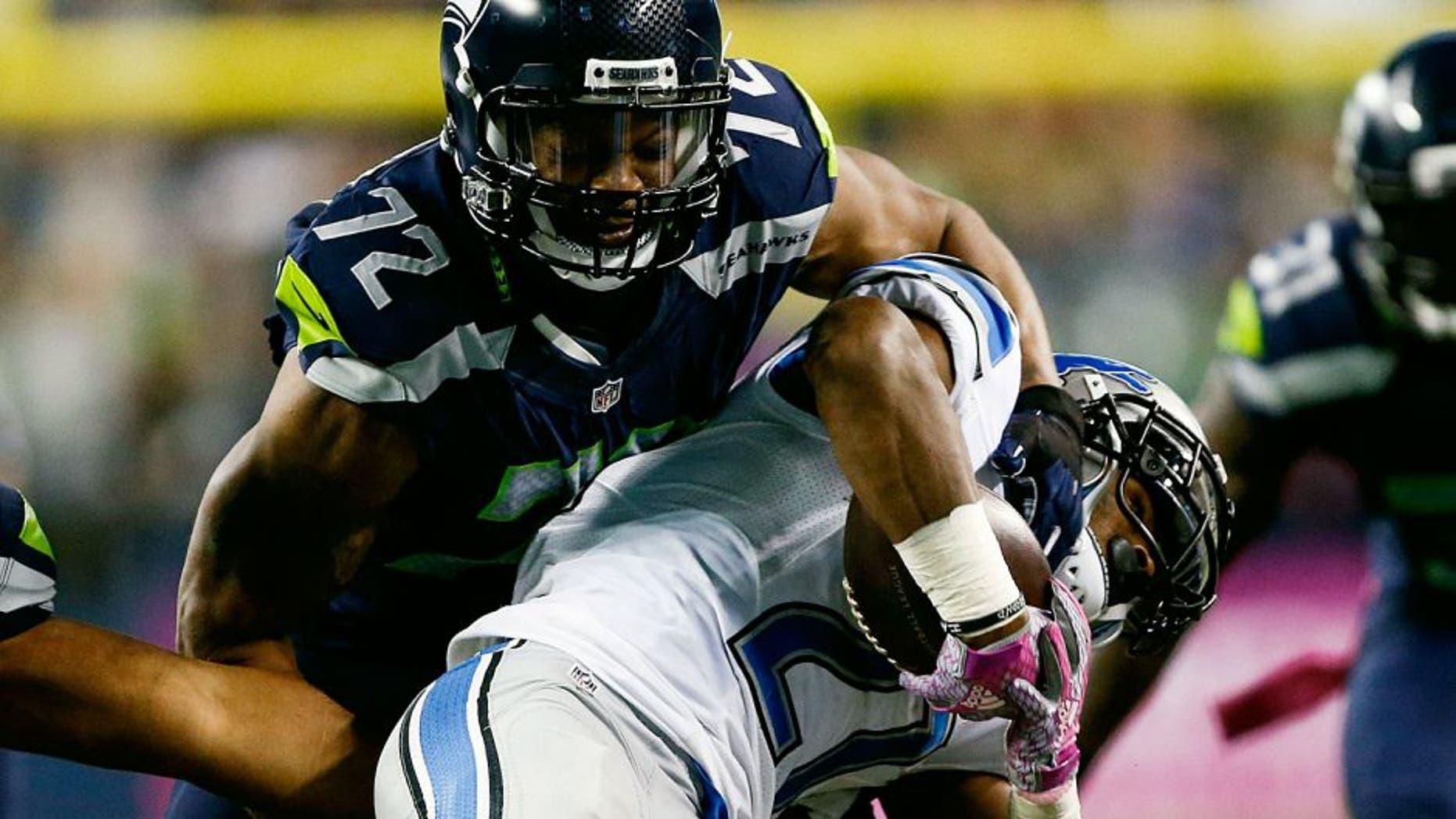 Oct 5, 2015; Seattle, WA, USA; Seattle Seahawks defensive end Michael Bennett (72) tackles Detroit Lions running back Ameer Abdullah (21) during the third quarter at CenturyLink Field. Mandatory Credit: Joe Nicholson-USA TODAY Sports