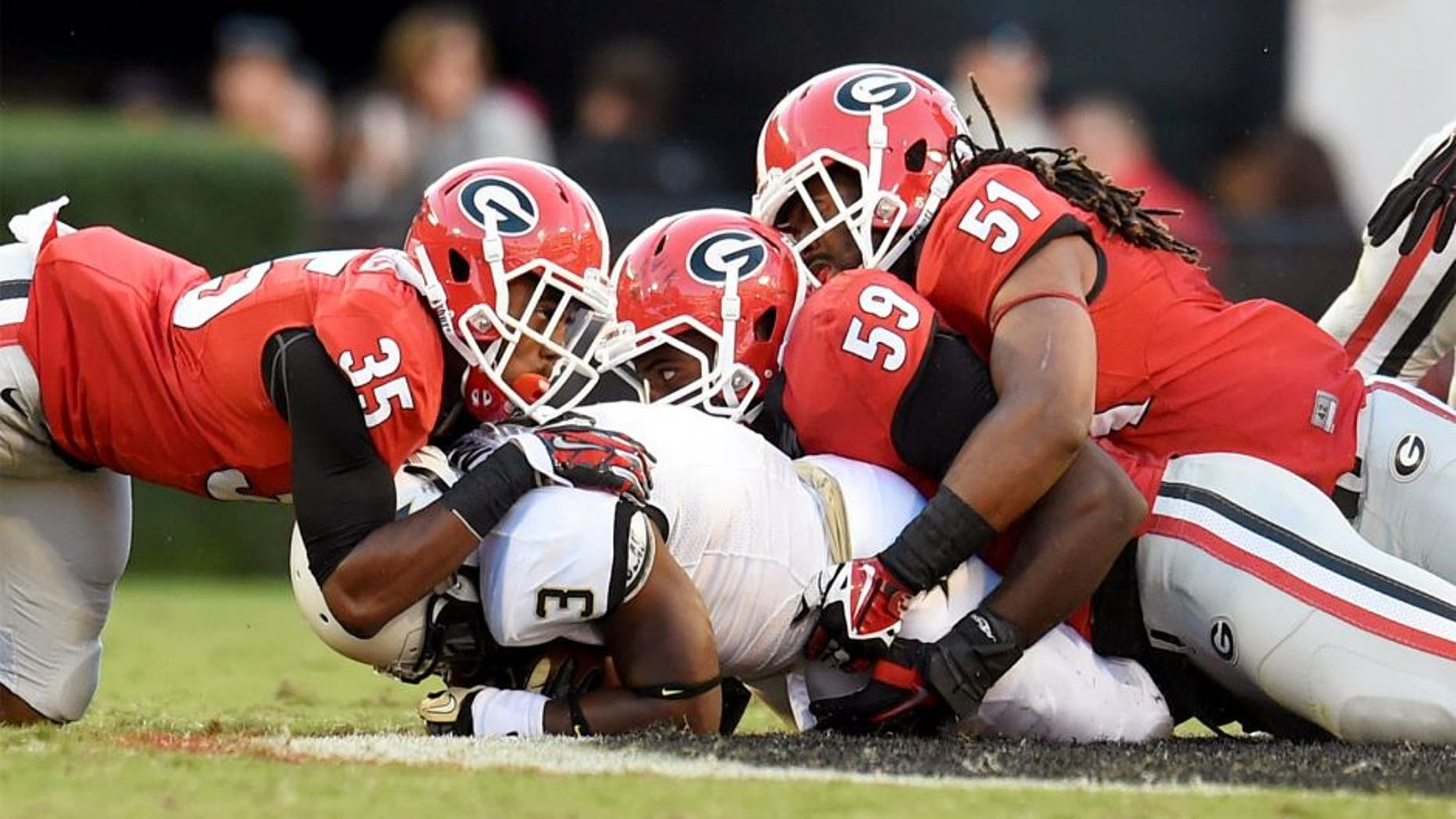 Oct 4, 2014; Athens, GA, USA; Vanderbilt Commodores running back Jerron Seymour (3) is tackled by Georgia Bulldogs cornerback Aaron Davis (35) linebacker Jordan Jenkins (59) and linebacker Ramik Wilson (51) during the second half at Sanford Stadium. Georgia defeated Vanderbilt 44-17. Mandatory Credit: Dale Zanine-USA TODAY Sports