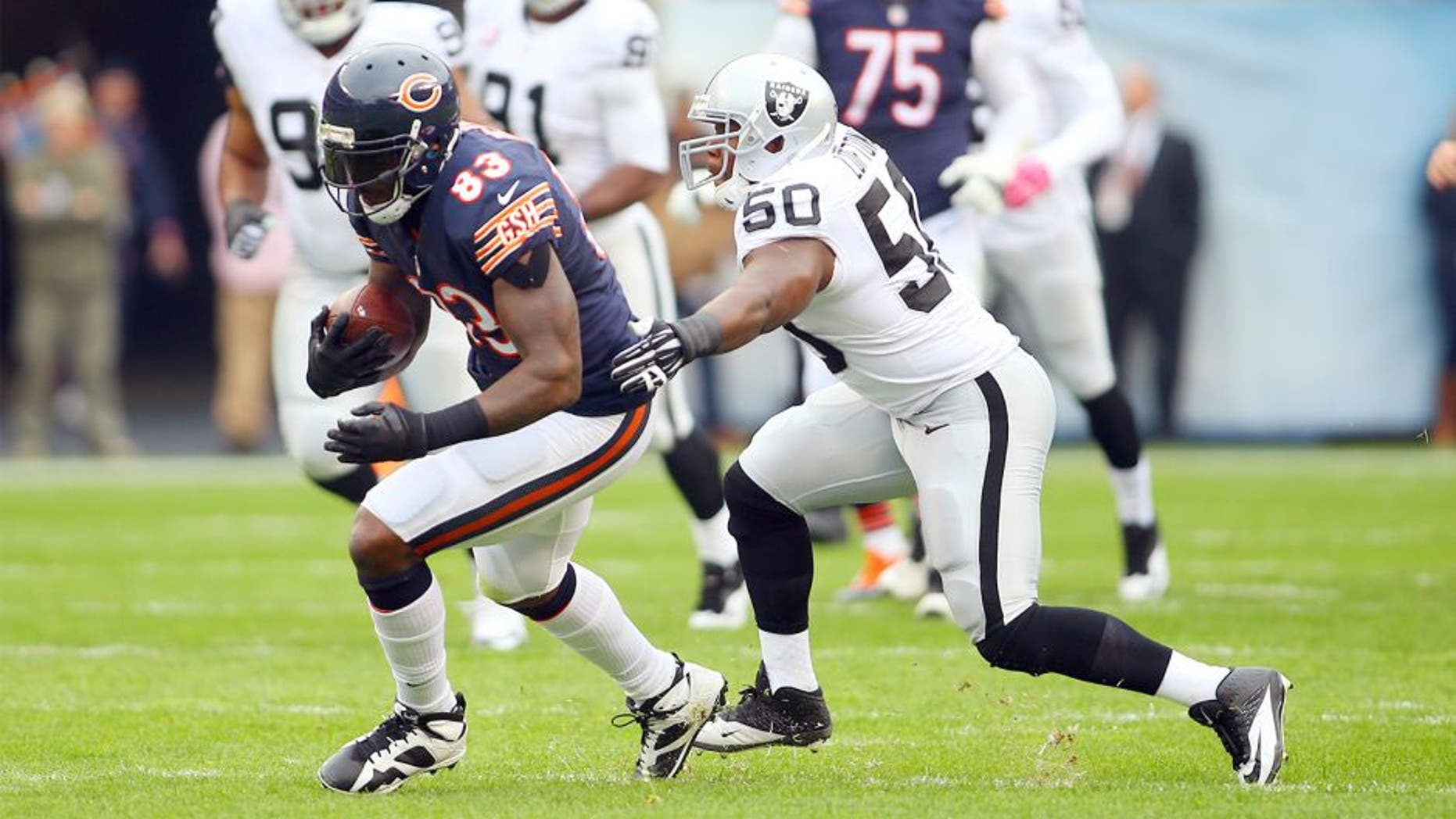 Oct 4, 2015; Chicago, IL, USA; Chicago Bears tight end Martellus Bennett (83) is tackled by Oakland Raiders middle linebacker Curtis Lofton (50) during the first quarter at Soldier Field. Mandatory Credit: Jerry Lai-USA TODAY Sports