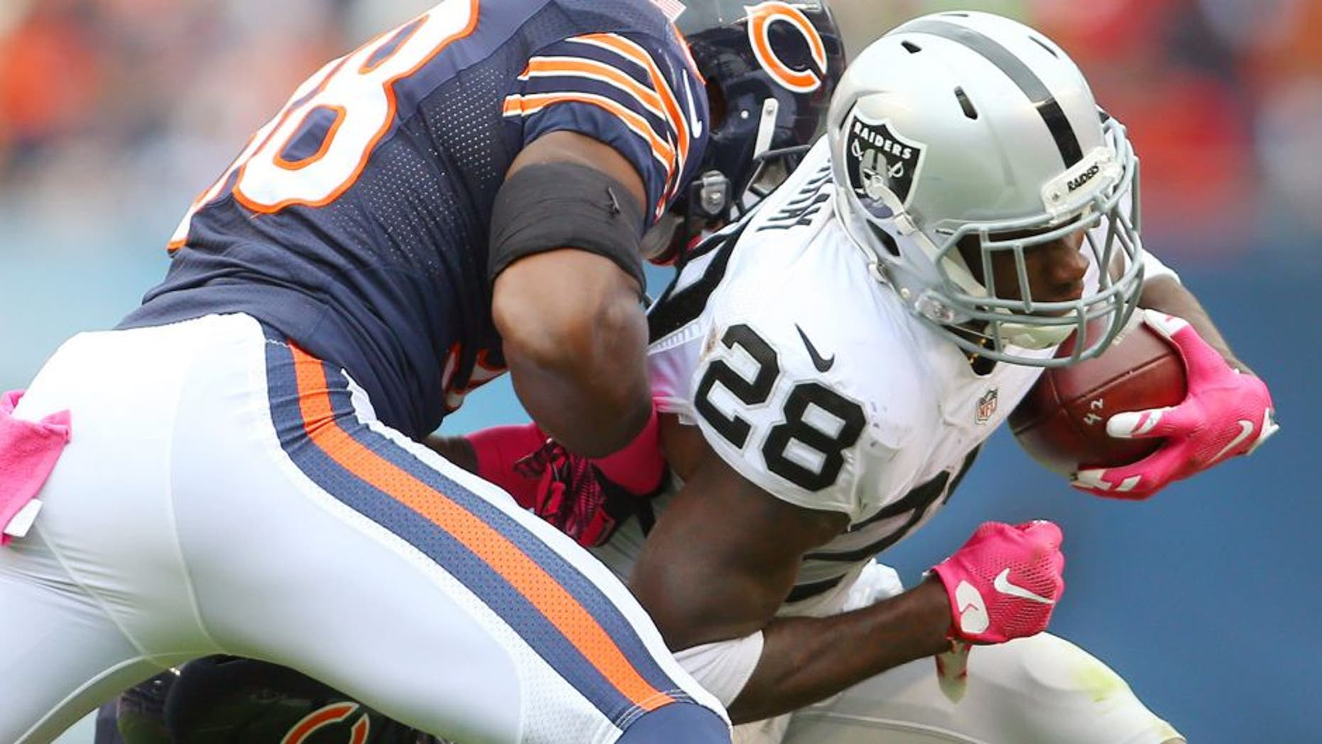 Oct 4, 2015; Chicago, IL, USA; Oakland Raiders running back Latavius Murray (28) is tackled by Chicago Bears free safety Adrian Amos (38) and linebacker Lamarr Houston (99) during the second quarter at Soldier Field. Mandatory Credit: Jerry Lai-USA TODAY Sports