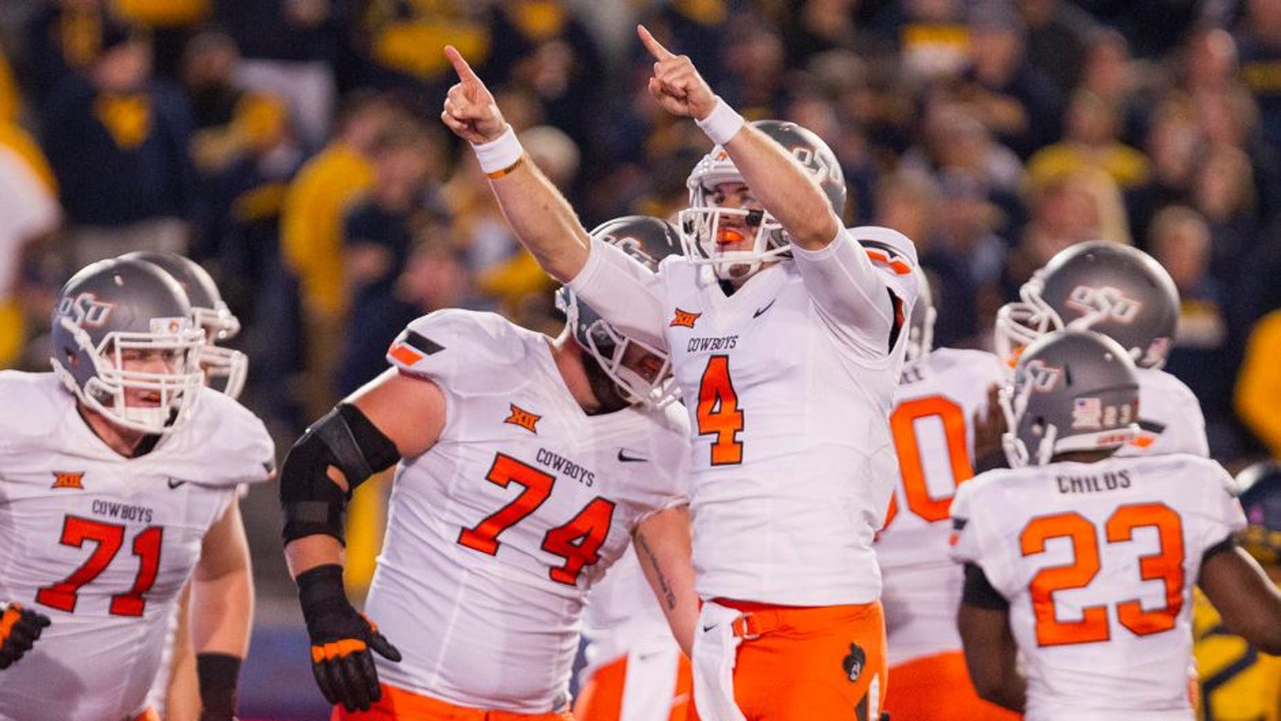 Oct 10, 2015; Morgantown, WV, USA; Oklahoma State Cowboys quarterback J.W Walsh celebrates after a touchdown during the third quarter against the West Virginia Mountaineers at Milan Puskar Stadium. Mandatory Credit: Ben Queen-USA TODAY Sports