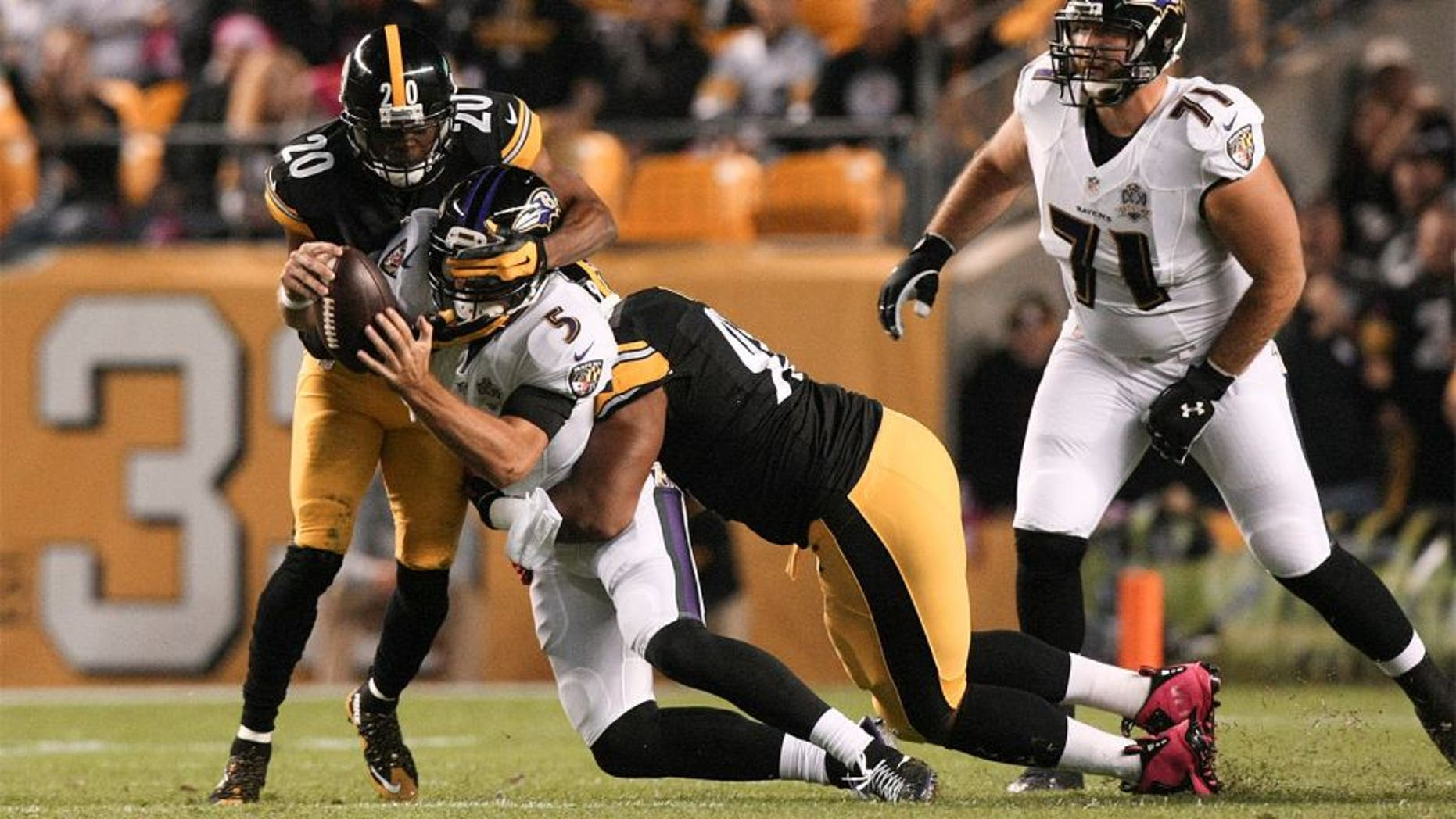 Oct 1, 2015; Pittsburgh, PA, USA; Baltimore Ravens quarterback Joe Flacco (5) is sacked by Pittsburgh Steelers safety Will Allen (20) and defensive end Stephon Tuitt (91) during the first quarter at Heinz Field. Mandatory Credit: Jason Bridge-USA TODAY Sports