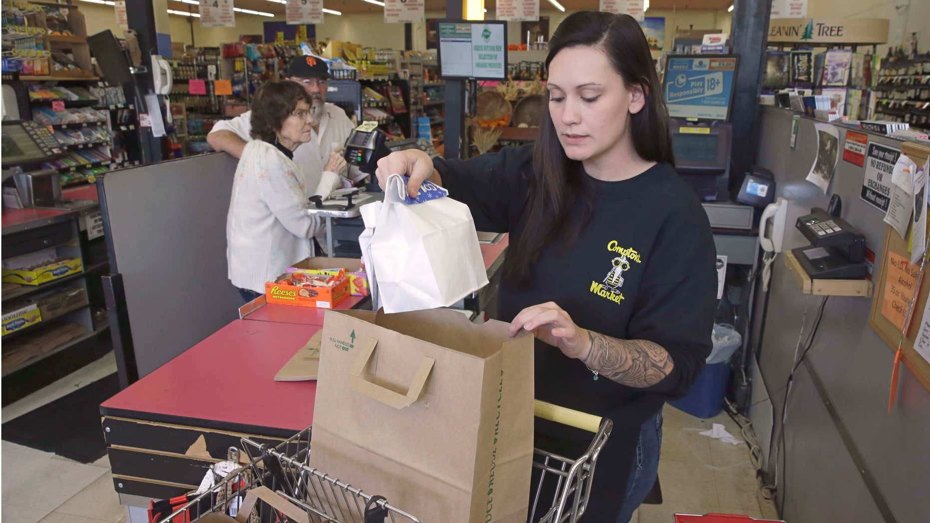 Oct. 6, 2015: Checker Brittney Bounds bags groceries for customer Esther Franklin, left, at Compton's Market in Sacramento, Calif. Calif.