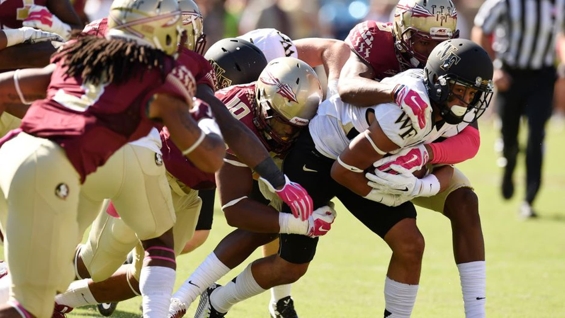 Oct 4, 2014; Tallahassee, FL, USA; Wake Forest Demon Deacons wide receiver Jared Crump (88) gets wrapped up by Florida State Seminoles linebacker E.J. Levenberry (10) and defensive back Jalen Ramsey (8) during the first quarter at Doak Campbell Stadium. Mandatory Credit: John David Mercer-USA TODAY Sports