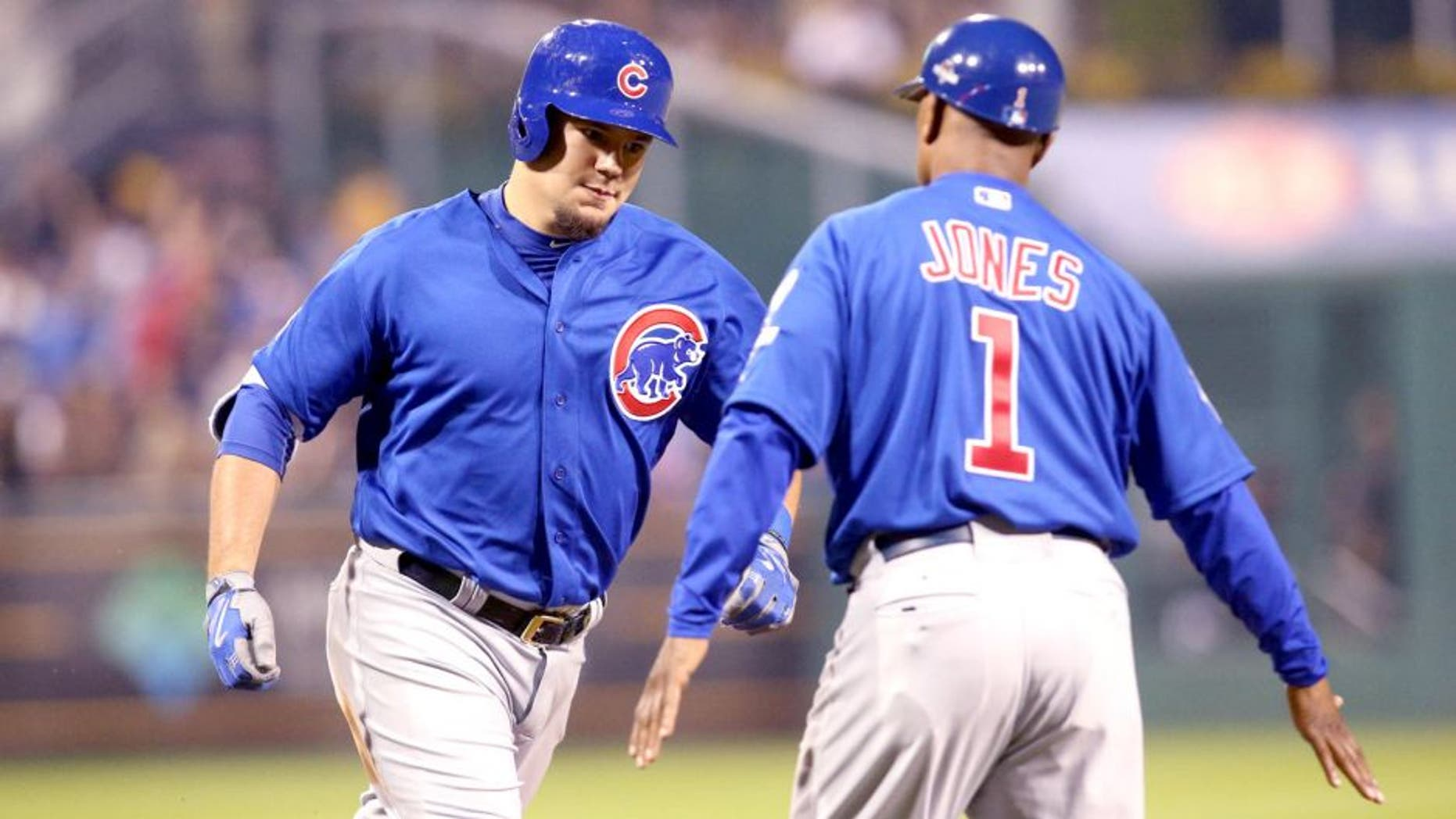 Oct 7, 2015; Pittsburgh, PA, USA; Chicago Cubs right fielder Kyle Schwarber (12) high fives third base coach Gary Jones (1) after hitting a two-run home run against the Pittsburgh Pirates during the third inning in the National League Wild Card playoff baseball game at PNC Park. Mandatory Credit: Charles LeClaire-USA TODAY Sports