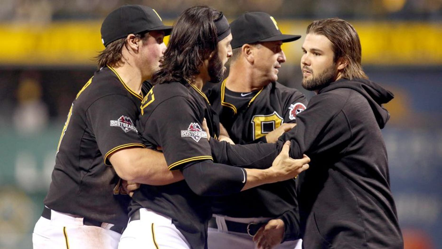 Oct 7, 2015; Pittsburgh, PA, USA; Pittsburgh Pirates first baseman Sean Rodriguez (3) is held back by teammates during an altercation with the Chicago Cubs during the seventh inning in the National League Wild Card playoff baseball game at PNC Park. Rodriguez was ejected from the game. Mandatory Credit: Charles LeClaire-USA TODAY Sports