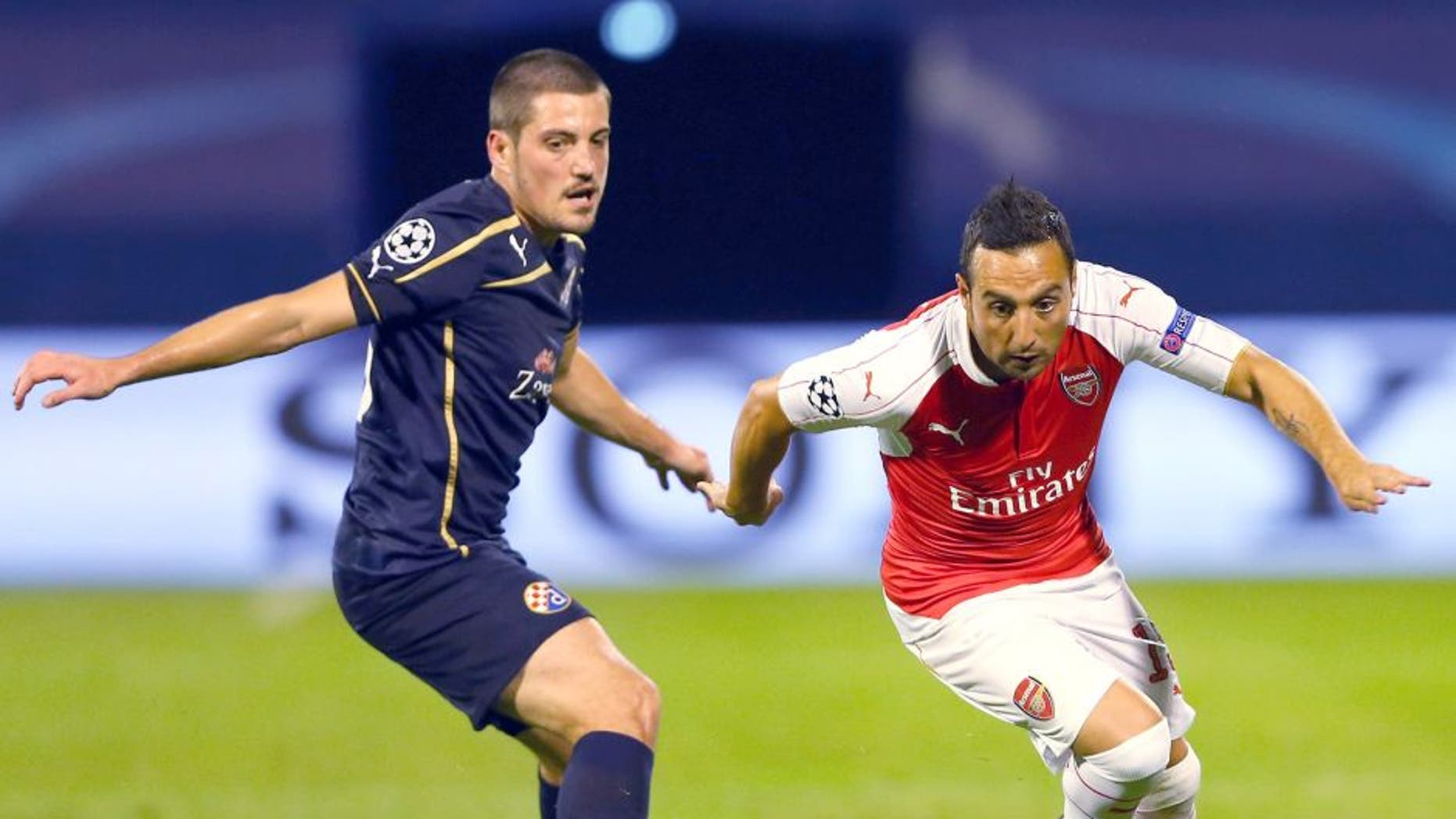 ZAGREB, CROATIA - SEPTEMBER 16: Santi Cazorla of Arsenal goes past Arijan Ademi of Dinamo Zagreb during the UEFA Champions League Group F match between Dinamo Zagreb and Arsenal at Maksimir Stadium on September 16, 2015 in Zagreb, Croatia. (Photo by Alexander Hassenstein/Getty Images)