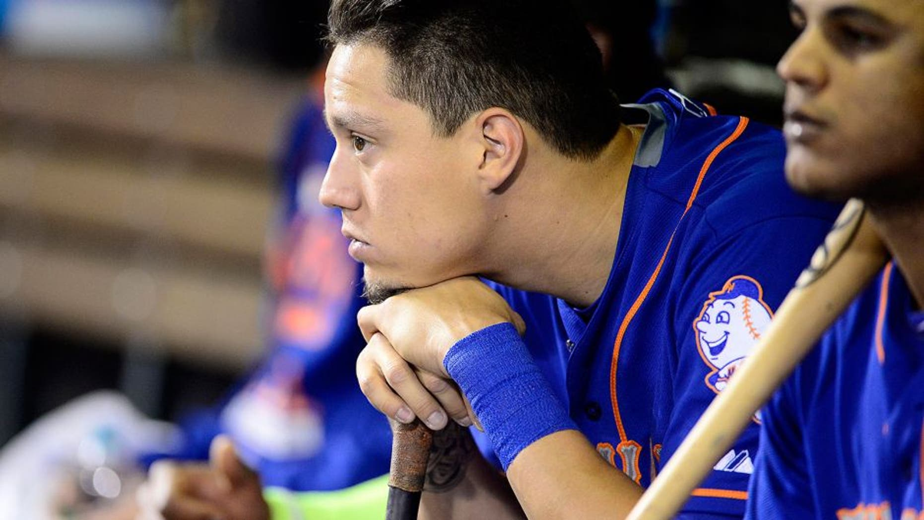 Aug 22, 2015; Denver, CO, USA; New York Mets shortstop Wilmer Flores (4) in his dugout in the ninth inning against the Colorado Rockies at Coors Field. The Mets defeated the Rockies 14-9. Mandatory Credit: Ron Chenoy-USA TODAY Sports
