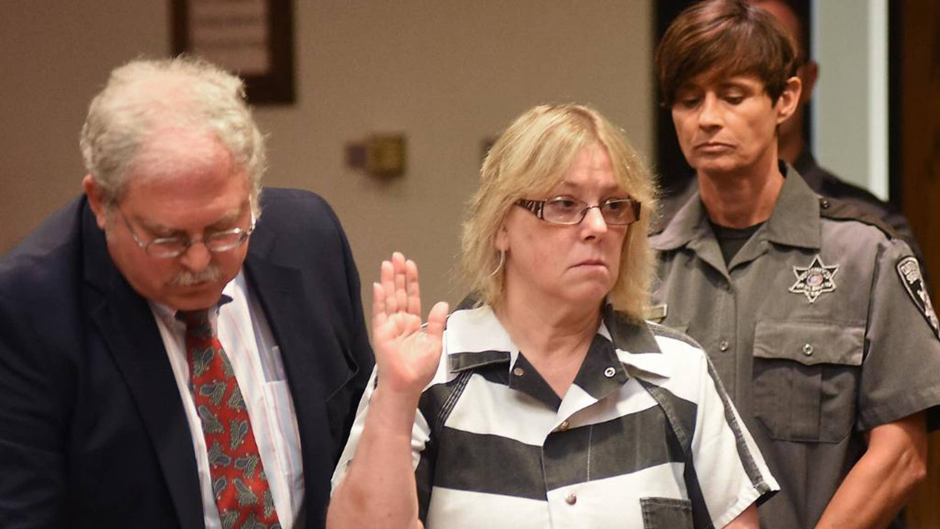 """FILE - In this July 28, 2015 file photo, Joyce Mitchell raises her hand during a court appearance in Plattsburgh, N.Y.  Mitchell, the former New York prison employee who helped two killers escape from a maximum-security prison in June, said in an interview that aired Monday, Sept. 14, on NBC's """"Today"""" show that she was depressed at the time and the inmates took advantage of what she called her """"weakness."""" (Rob Fountain/The Press-Republican via AP, Pool, File)"""