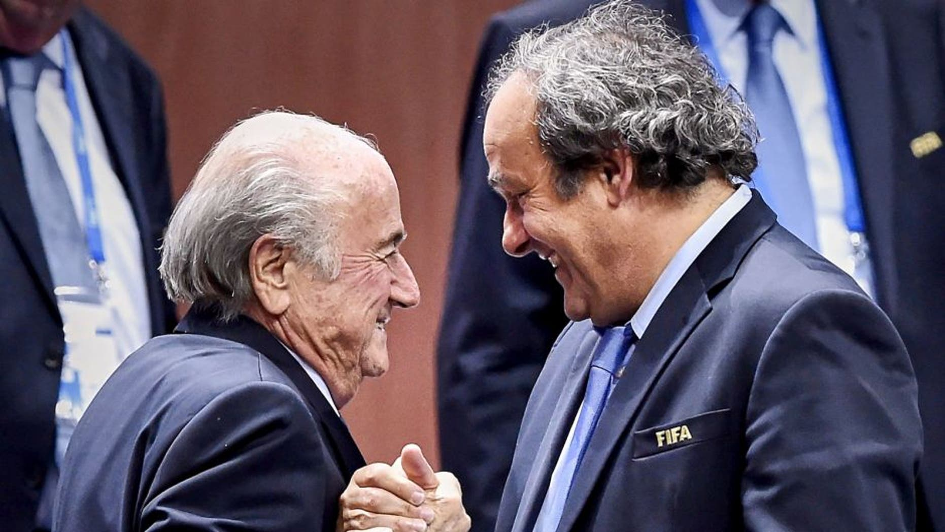 FIFA President Sepp Blatter (Foreground-L) shakes hands with UEFA president Michel Platini after being re-elected following a vote to decide on the FIFA presidency in Zurich on May 29, 2015. Sepp Blatter won the FIFA presidency for a fifth time after his challenger Prince Ali bin al Hussein withdrew just before a scheduled second round. AFP PHOTO / MICHAEL BUHOLZER (Photo credit should read MICHAEL BUHOLZER/AFP/Getty Images)