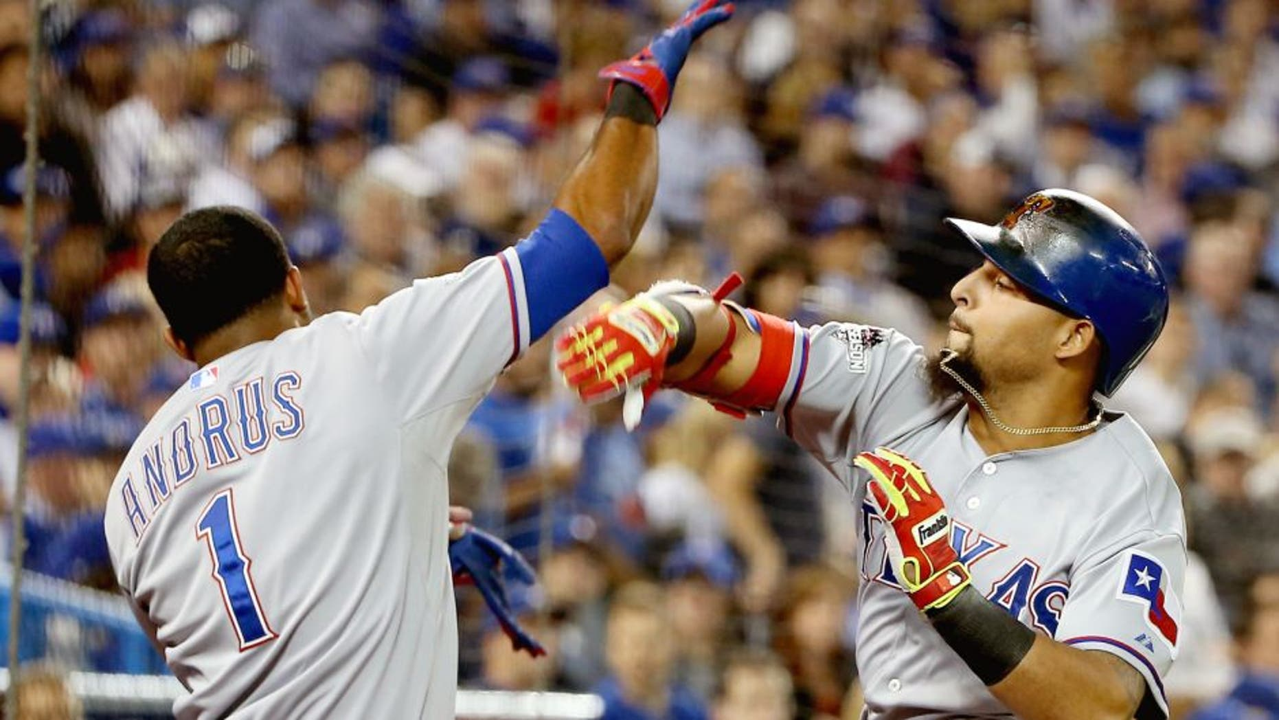Rougned Odor #12 of the Texas Rangers celebrates with teammate Elvis Andrus #1 after scoring a solo home run against David Price #14 of the Toronto Blue Jays in the seventh inning during game one of the American League Division Series at Rogers Centre on October 8, 2015 in Toronto, Ontario, Canada. (Photo by Tom Szczerbowski/Getty Images)
