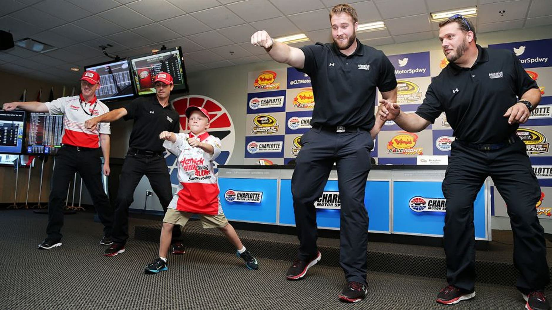 CHARLOTTE, NC - OCTOBER 08: Crew chief for Kasey Kahne, driver of the #5 HendrickRideAlong.com Chevrolet, Keith Rodden (L), crew members and honorary crew chief Braylon Beam (C) dance during a press conference prior to qualifying for the NASCAR Sprint Cup Series Bank of America 500 at Charlotte Motor Speedway on October 8, 2015 in Charlotte, North Carolina. (Photo by Jerry Markland/Getty Images)