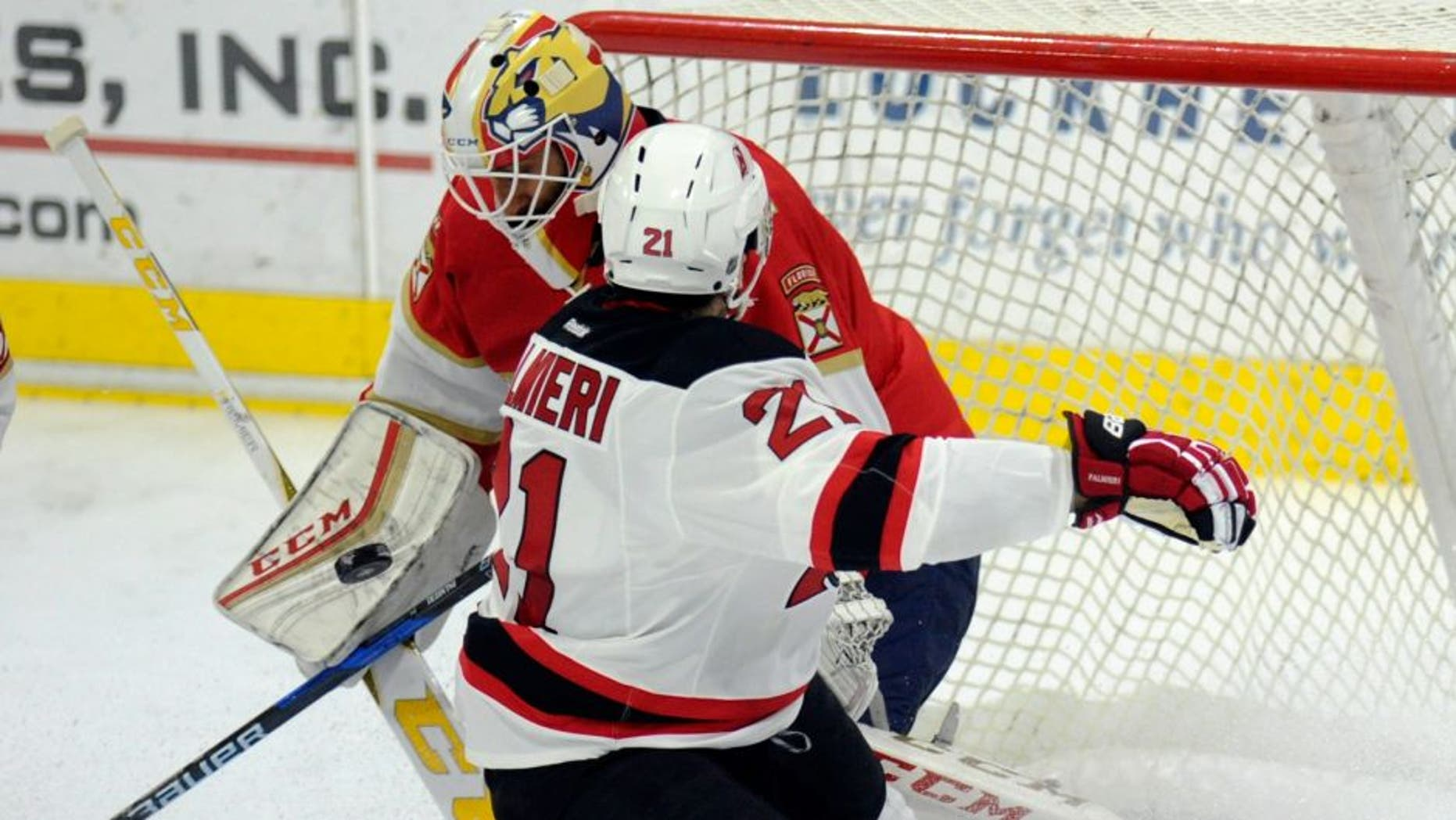 Florida Panthers goalie Roberto Luongo (1) deflects a shot by New Jersey Devils right wing Kyle Palmieri (21) during the first period of an NHL preseason hockey game, Saturday, Oct. 8, 2016, in West Point, N.Y. (AP Photo/Hans Pennink)