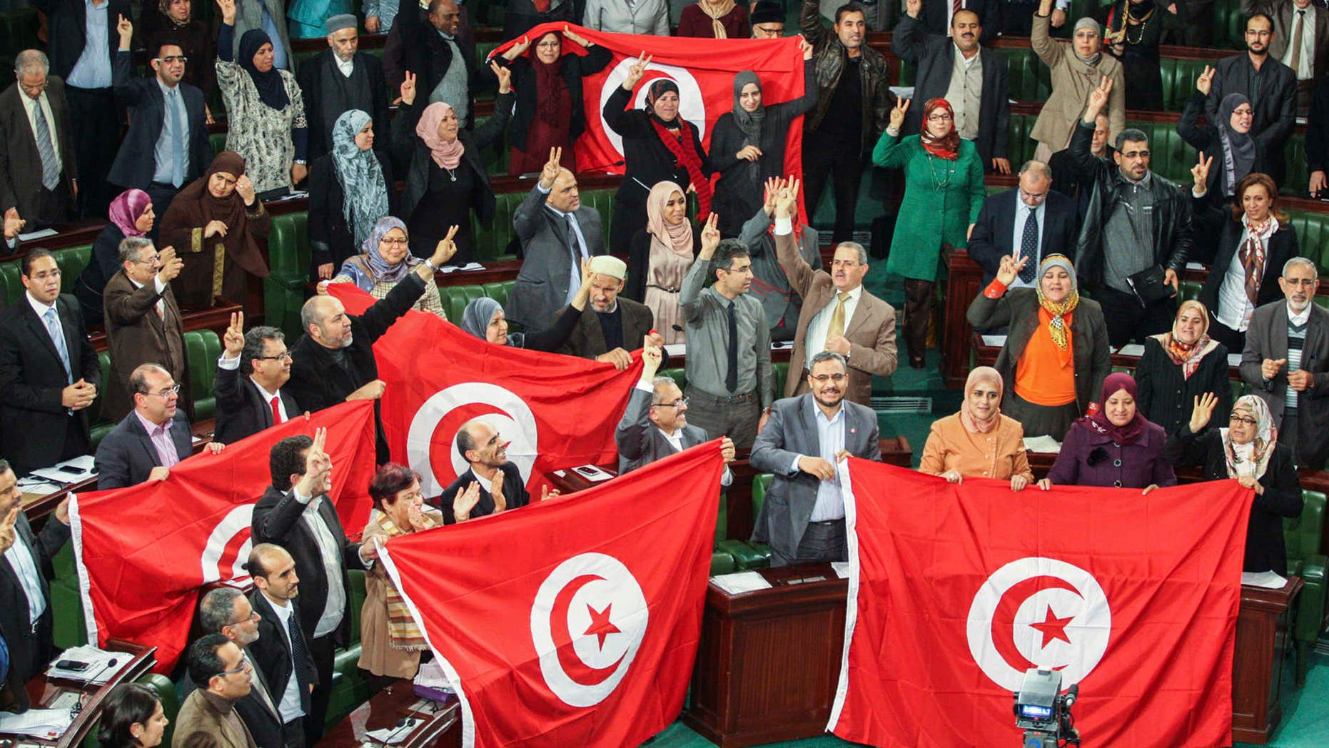 FILE - In this Sunday, Jan. 26, 2014 file photo, members of the Tunisian National Constituent Assembly celebrate the adoption of the new constitution in Tunis, Tunisia.