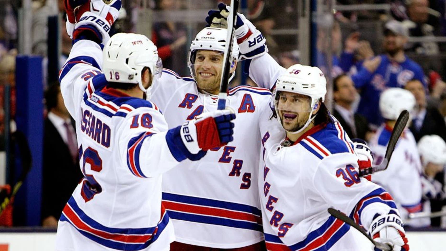 New York Rangers' Mats Zuccarello, right, celebrates his goal against the Columbus Blue Jackets with teammates Derick Brassard, left, and Dan Girardi during the third period of an NHL hockey game Friday, Oct. 9, 2015, in Columbus, Ohio. The Rangers beat the Blue Jackets 4-2. (AP Photo/Jay LaPrete)