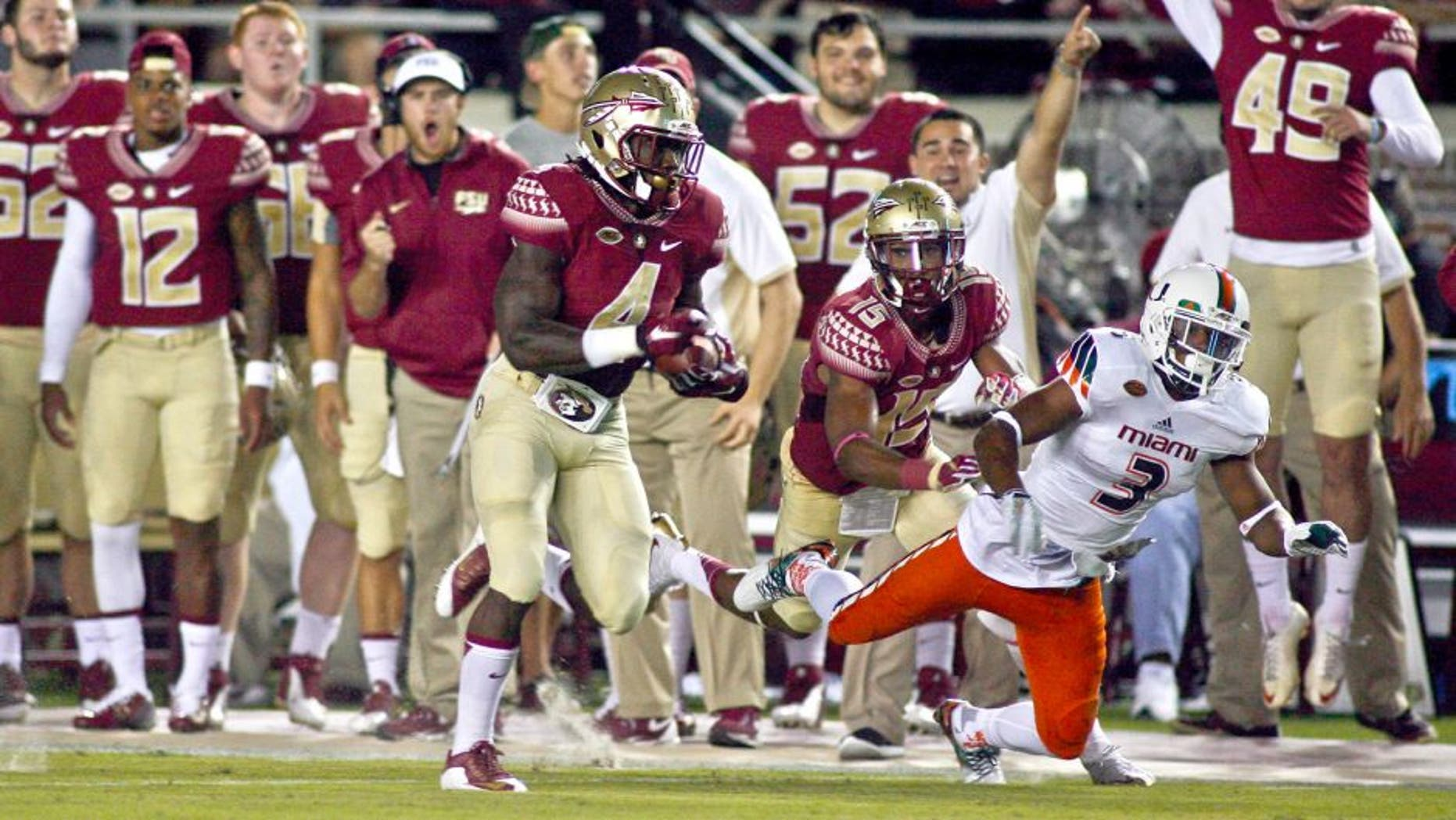 Oct 10, 2015; Tallahassee, FL, USA; With a block on Miami Hurricanes defensive back Tracy Howard (3) by Florida State Seminoles wide receiver Travis Rudolph (15), Florida State Seminoles running back Dalvin Cook (4) runs for a 72-yard touchdown in the first quarter of their game at Doak Campbell Stadium. Mandatory Credit: Phil Sears-USA TODAY Sports