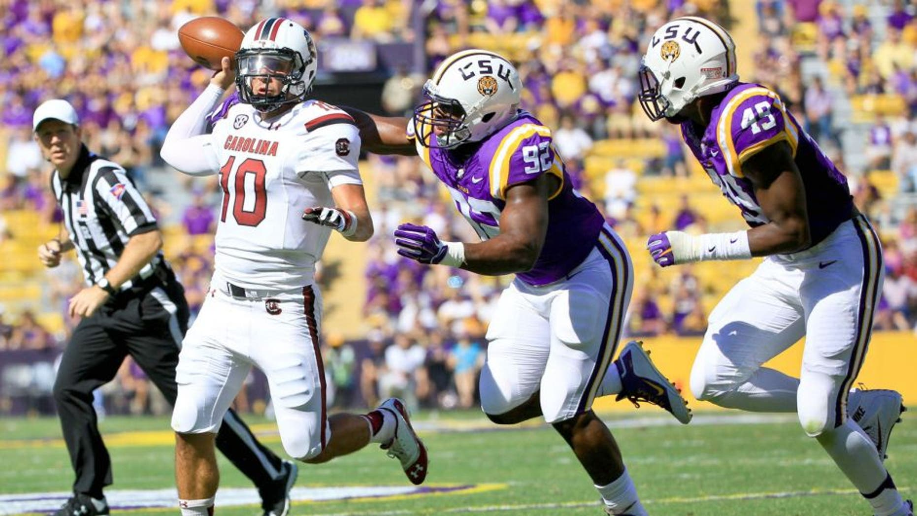 Oct 10, 2015; Baton Rouge, LA, USA; South Carolina Gamecocks quarterback Perry Orth (10) is pressured by LSU Tigers defensive end Lewis Neal (92) during the first quarter of a game at Tiger Stadium. Mandatory Credit: Derick E. Hingle-USA TODAY Sports