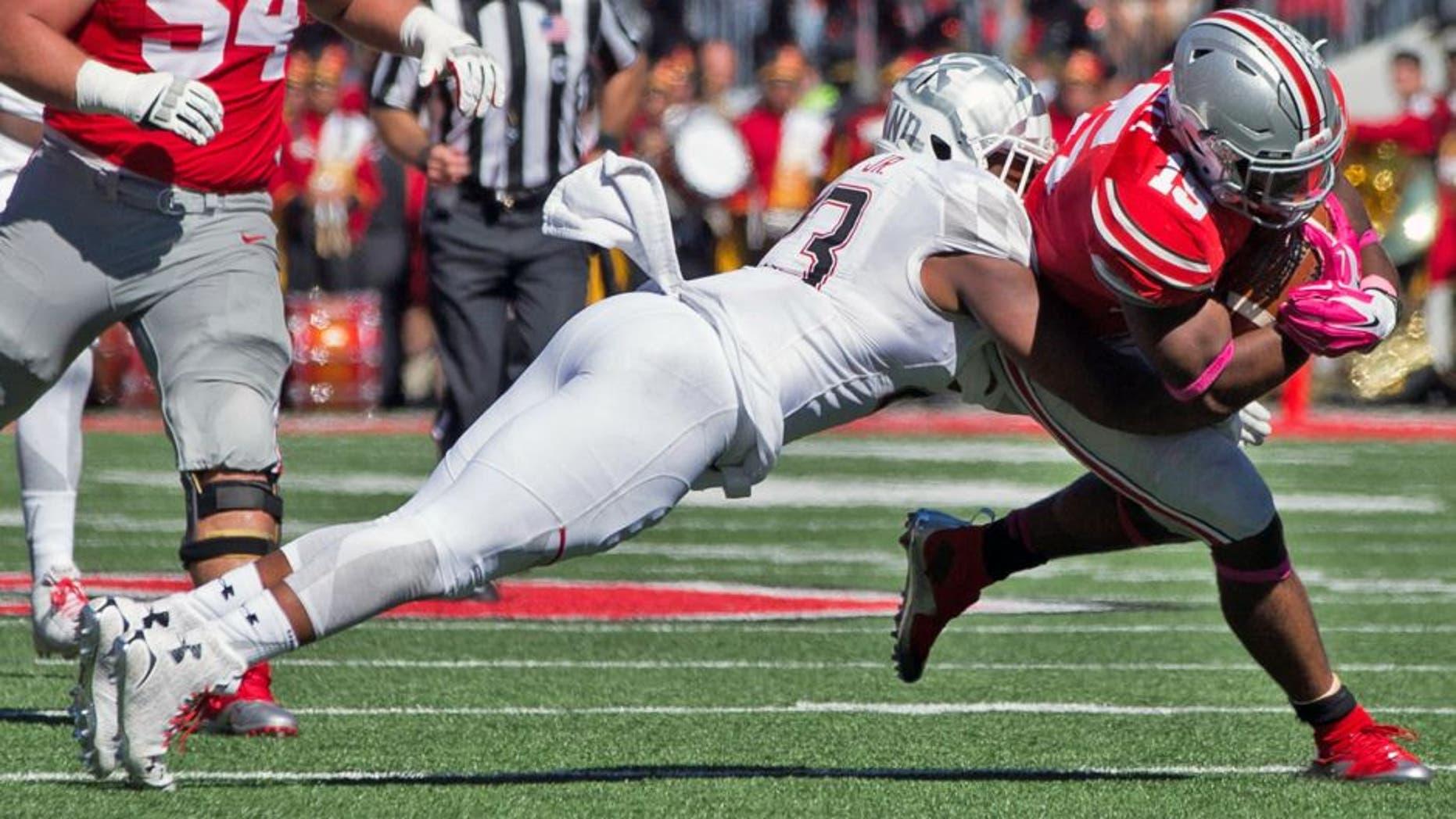 Oct 10, 2015; Columbus, OH, USA; Maryland Terrapins linebacker Jermaine Carter Jr. (23) tackles Ohio State Buckeyes running back Ezekiel Elliott (15) at Ohio Stadium. Mandatory Credit: Greg Bartram-USA TODAY Sports