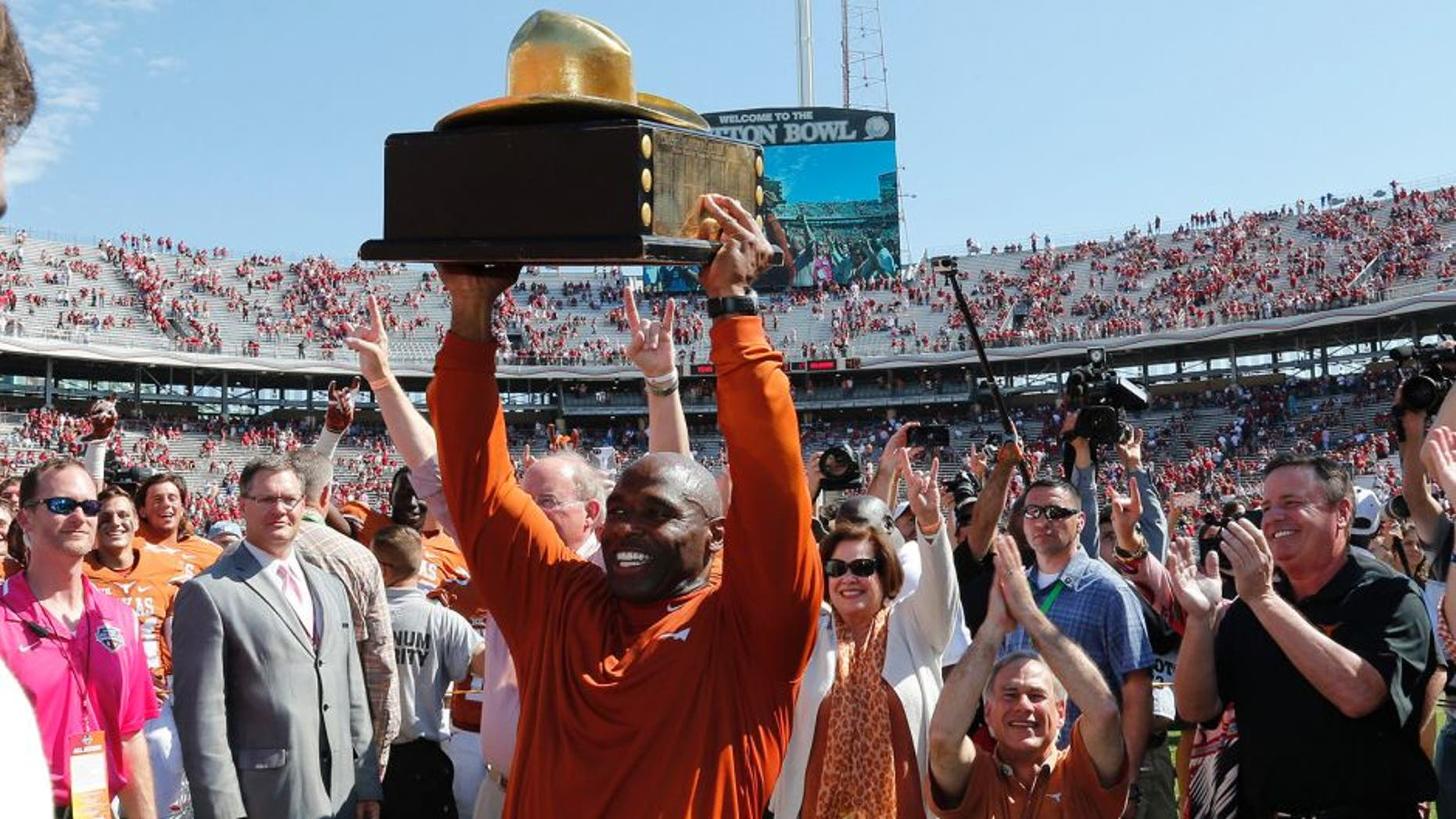 Oct 10, 2015; Dallas, TX, USA; Texas Longhorns head coach Charlie Strong celebrates with the golden hat trophy after a victory against the Oklahoma Sooners during Red River rivalry at Cotton Bowl Stadium. Texas beat Oklahoma 24-17. Mandatory Credit: Matthew Emmons-USA TODAY Sports