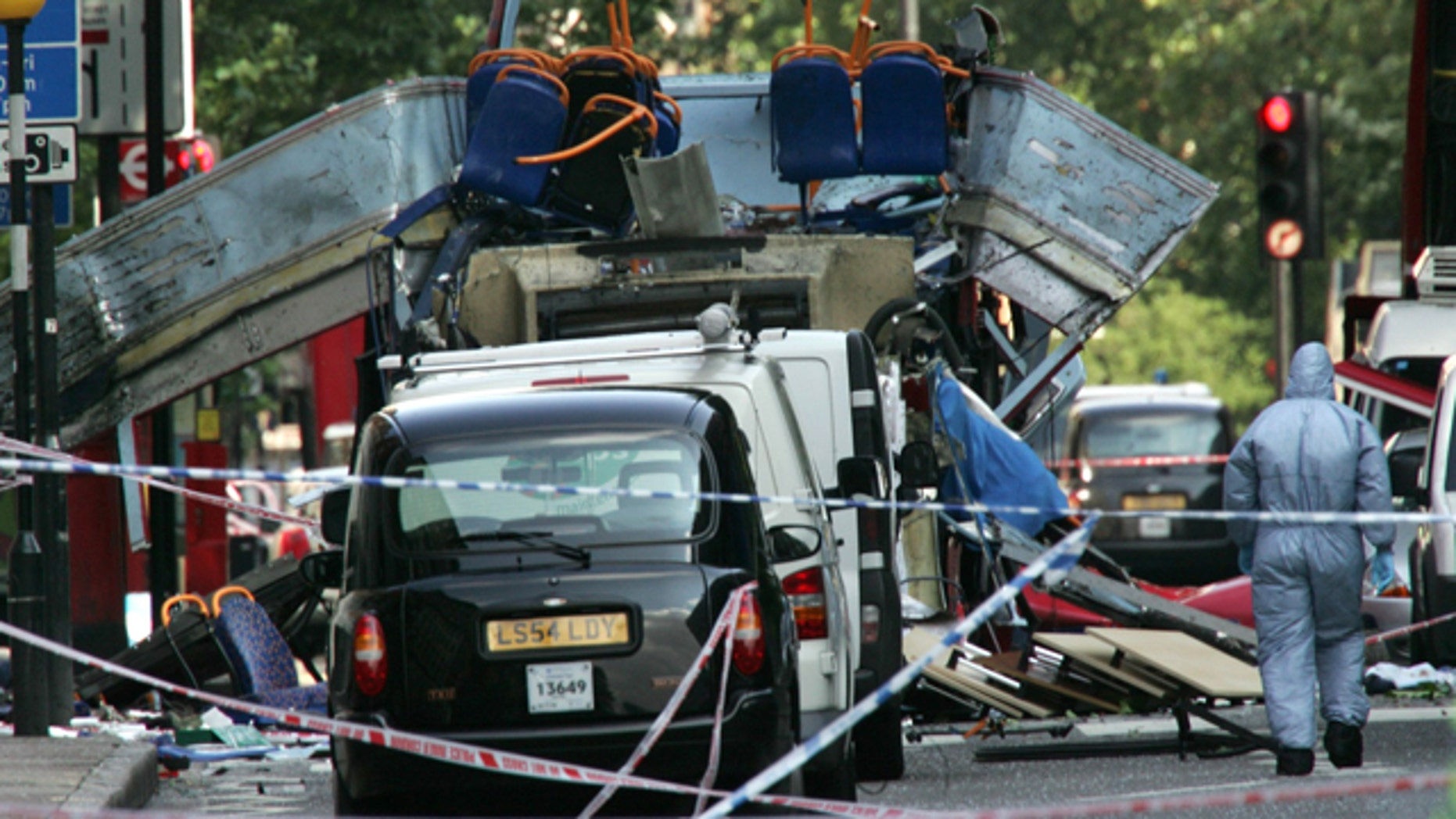 In this July 7, 2005 file photo, a forensic officer walks next to the wreckage of a double decker bus with its top blown off and damaged cars scattered on the road at Tavistock Square in central London.