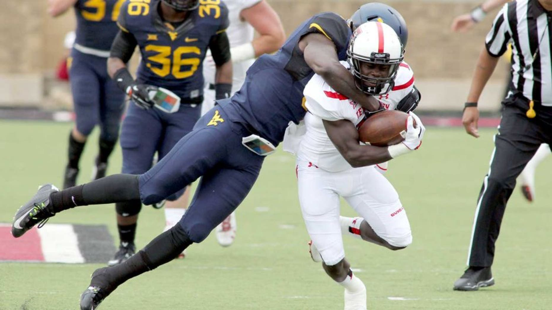 Oct 11, 2014; Lubbock, TX, USA; Texas Tech Red Raiders wide receiver Jakeem Grant (11) is tackled by West Virginia Mountaineers defensive back K.J. Dillion (9) in the first half at Jones AT&T Stadium. Mandatory Credit: Michael C. Johnson-USA TODAY Sports