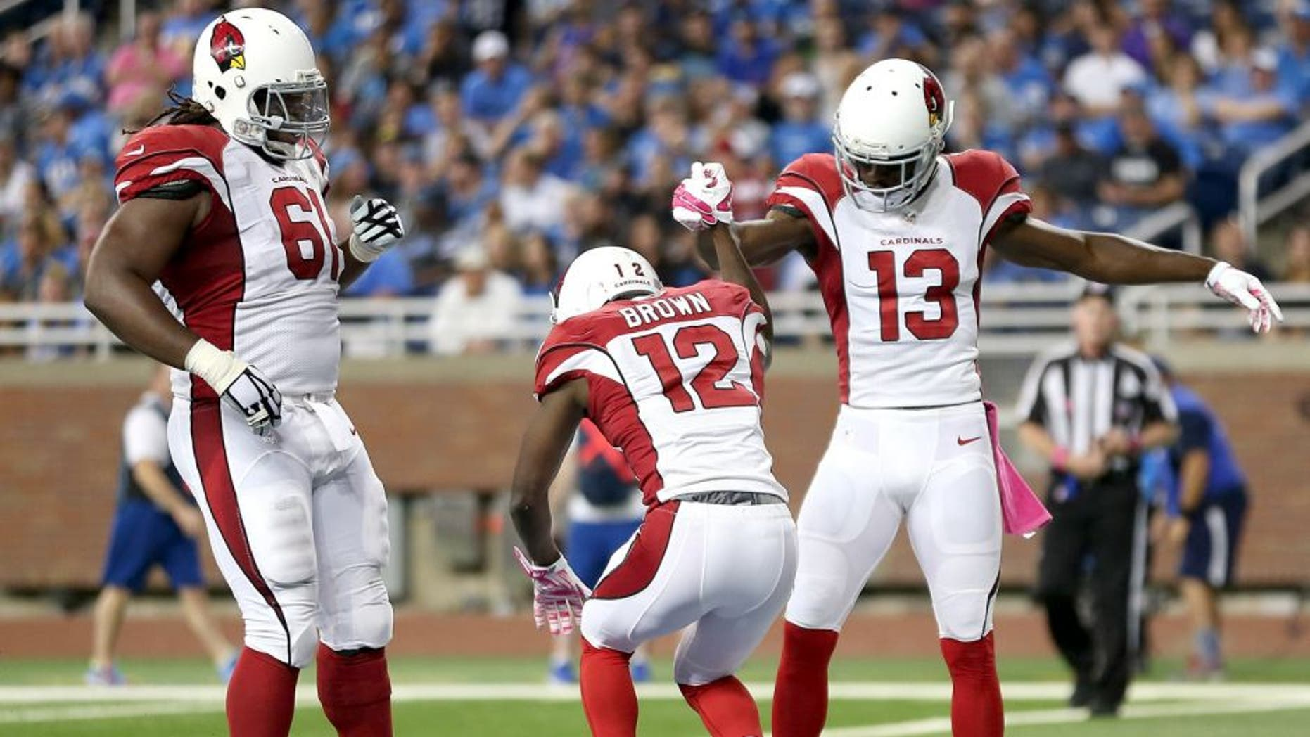 DETROIT MI - OCTOBER 11: John Brown of the Arizona Cardinals celebrates his second-quarter touchdown against the Detroit Lions with teammates Jaron Brown and Jonathan Cooper on October 11, 2015 at Ford Field in Detroit, Michigan. (Photo by Leon Halip/Getty Images)