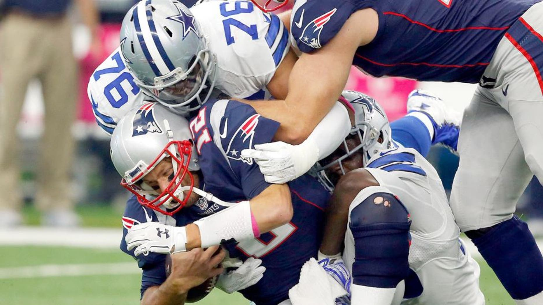 Oct 11, 2015; Arlington, TX, USA; New England Patriots quarterback Tom Brady (12) is sacked by Dallas Cowboys linebacker Rolando McClain (55) and defensive end Greg Hardy (76) at AT&T Stadium. Patriots tackle Nate Solder (77) trying to block out Hardy (76). Mandatory Credit: Erich Schlegel-USA TODAY Sports