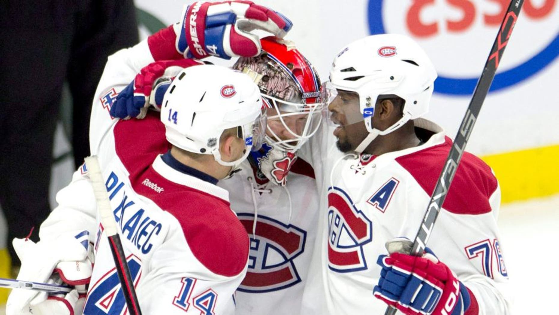 Montreal Canadiens defenseman P.K. Subban, right, and center Tomas Plekanec congratulate goalie Mike Condon as the Canadiens defeat the Ottawa Senators in an NHL hockey game, Sunday, Oct. 11, 2015 in Ottawa, Ontario. (Adrian Wyld/The Canadian Press via AP) MANDATORY CREDIT