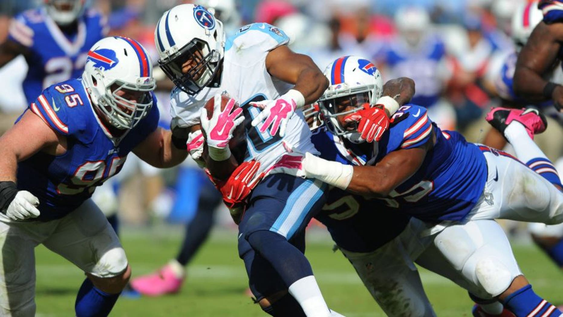 Oct 11, 2015; Nashville, TN, USA; Tennessee Titans running back Bishop Sankey (20) is tackled by Buffalo Bills defensive end Jerry Hughes (55) and defensive tackle Kyle Williams (95) during the second half at Nissan Stadium. The Bills won 14-13. Mandatory Credit: Christopher Hanewinckel-USA TODAY Sports
