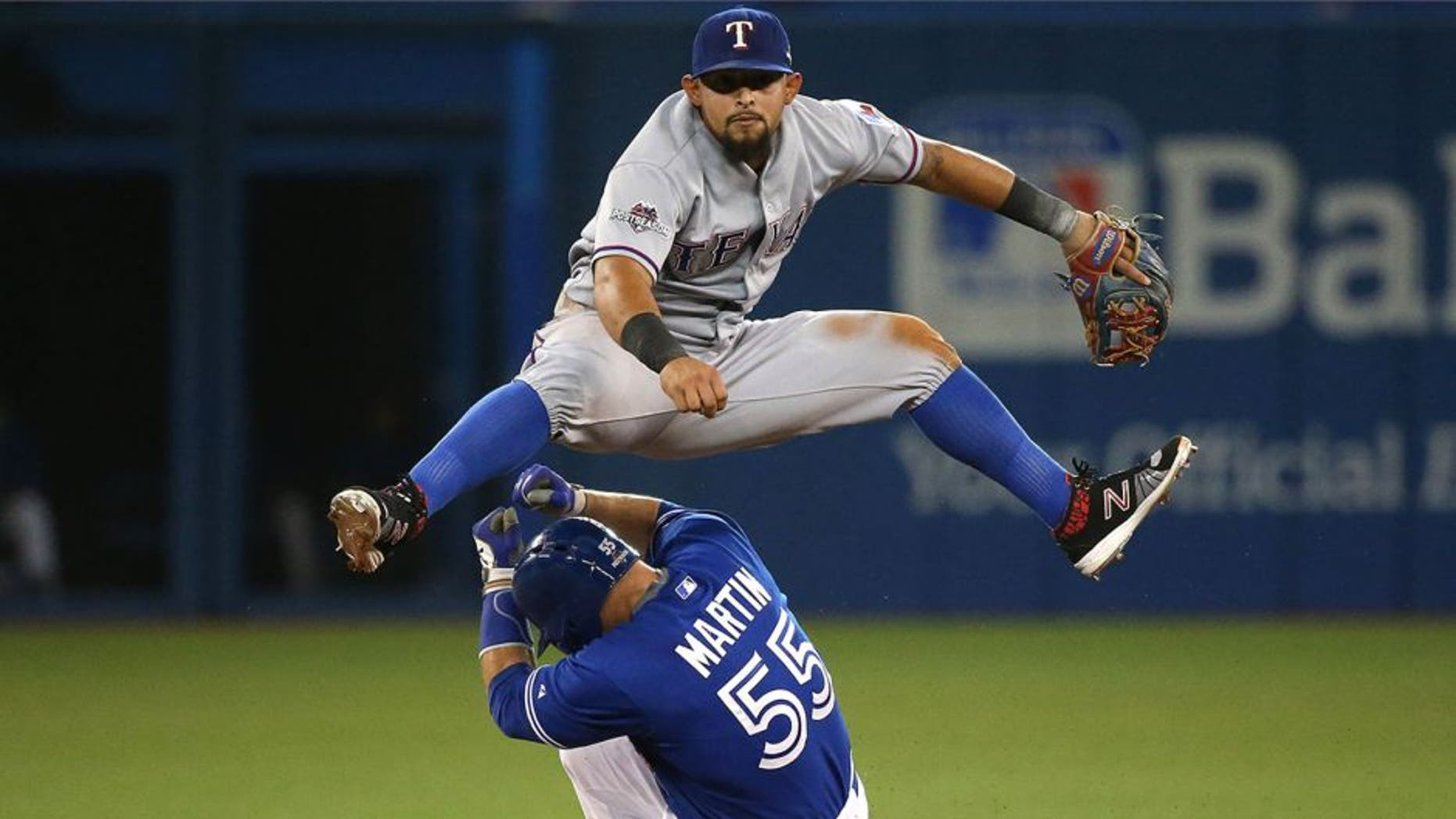 TORONTO, ON- OCTOBER 9: Joey Gallo leaps over Russell Martin turning a double play. The Toronto Blue Jays and Texas Rangers play game two of the MLB American League Division Series . at Rogers Centre in Toronto. October 9, 2015. (Steve Russell/Toronto Star via Getty Images)