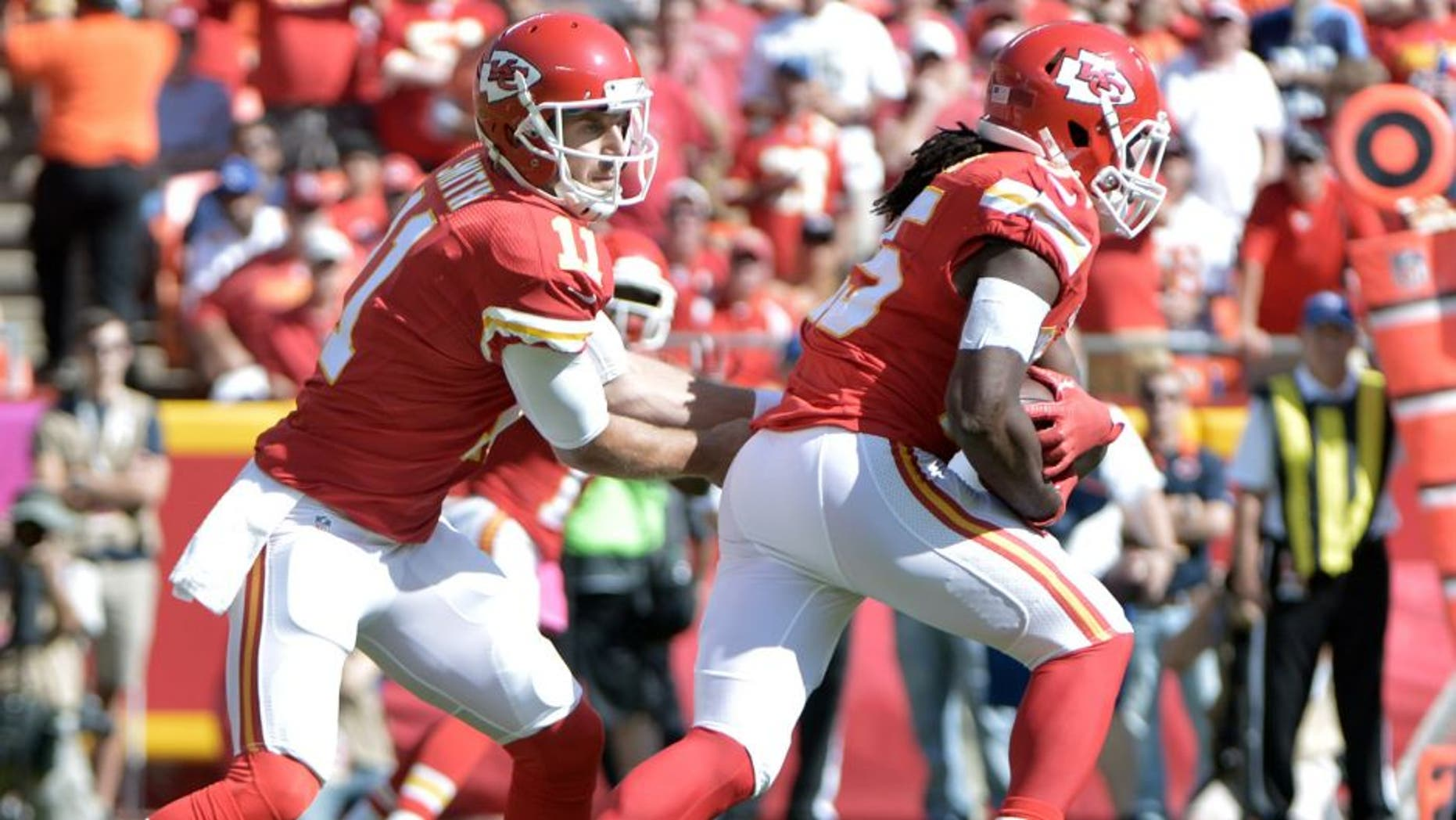 Oct 11, 2015; Kansas City, MO, USA; Kansas City Chiefs quarterback Alex Smith (11) hands off to running back Jamaal Charles (25) during the first half against the Chicago Bears at Arrowhead Stadium. Mandatory Credit: Denny Medley-USA TODAY Sports