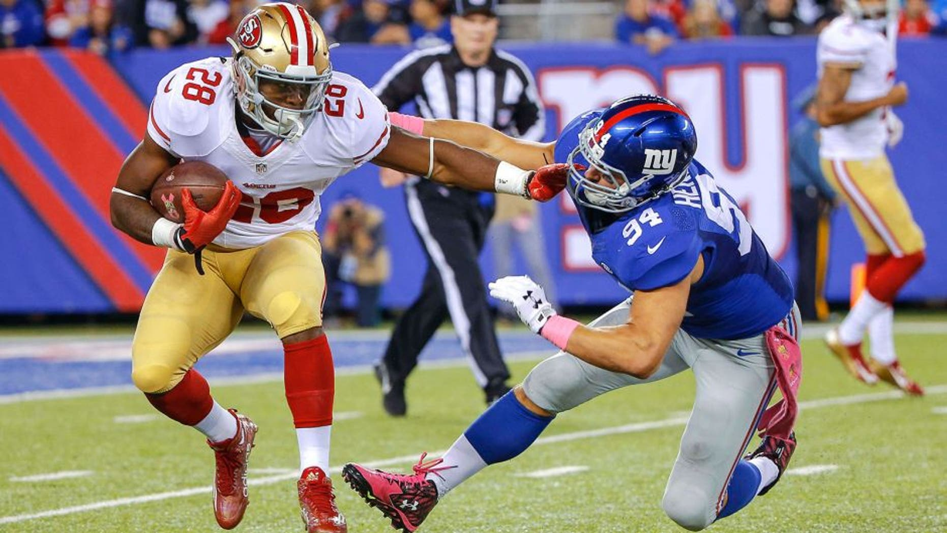 Oct 11, 2015; East Rutherford, NJ, USA; San Francisco 49ers running back Carlos Hyde (28) carries the ball as New York Giants outside linebacker Mark Herzlich (94) defends during the third quarter at MetLife Stadium. The Giants won 30-27. Mandatory Credit: Jim O'Connor-USA TODAY Sports