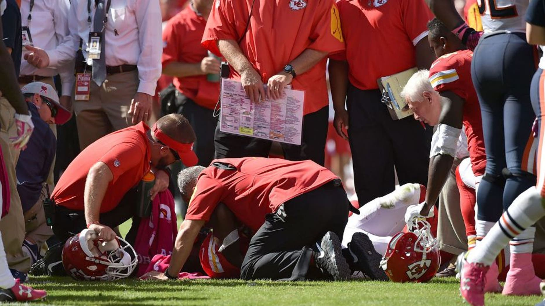 KANSAS CITY, MO - OCTOBER 11: Kansas City Chiefs training staff attends to an injury for Jamaal Charles #25 of the Kansas City Chiefs after a run with head coach Andy Reid of the Kansas City Chiefs overlooking at Arrowhead Stadium during the game against the Chicago Bears on October 11, 2015 in Kansas City, Missouri. (Photo by Peter Aiken/Getty Images)