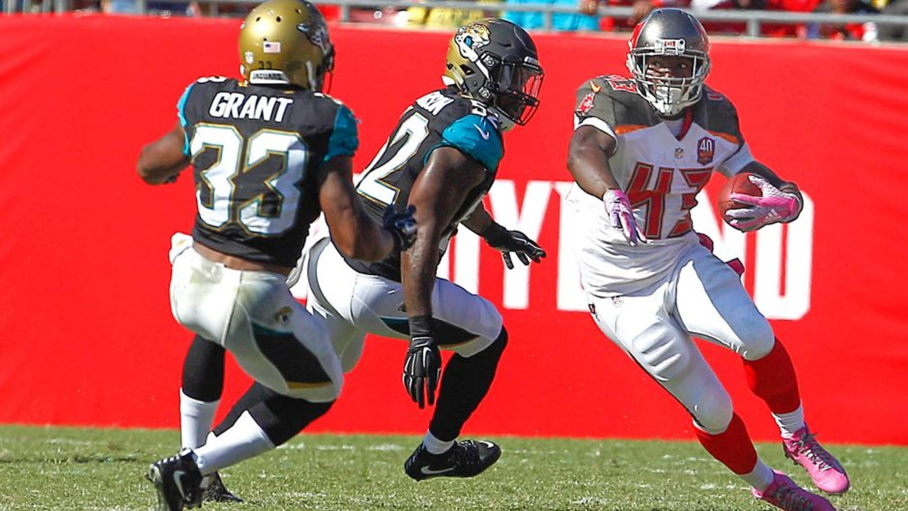 Oct 11, 2015; Tampa, FL, USA;Jacksonville Jaguars running back Corey Grant (33) and James Michael-Johnson (52) chase Tampa Bay Buccaneers running back Bobby Rainey (43) during the second half of an NFL football game at Raymond James Stadium. Tampa won 38-31. Mandatory Credit: Reinhold Matay-USA TODAY Sports