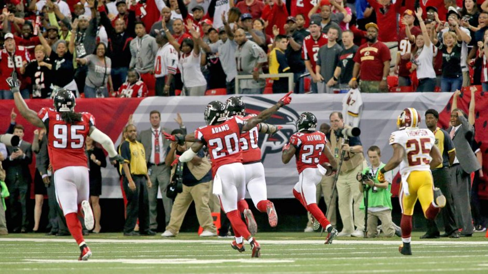 Oct 11, 2015; Atlanta, GA, USA; Atlanta Falcons defensive tackle Jonathan Babineaux (95) and defensive back Phillip Adams (20) celebrate as cornerback Robert Alford (23, right) returns an interception for a touchdown to win the game in overtime against the Washington Redskins at the Georgia Dome. The Falcons won 25-19 in overtime. Mandatory Credit: Jason Getz-USA TODAY Sports