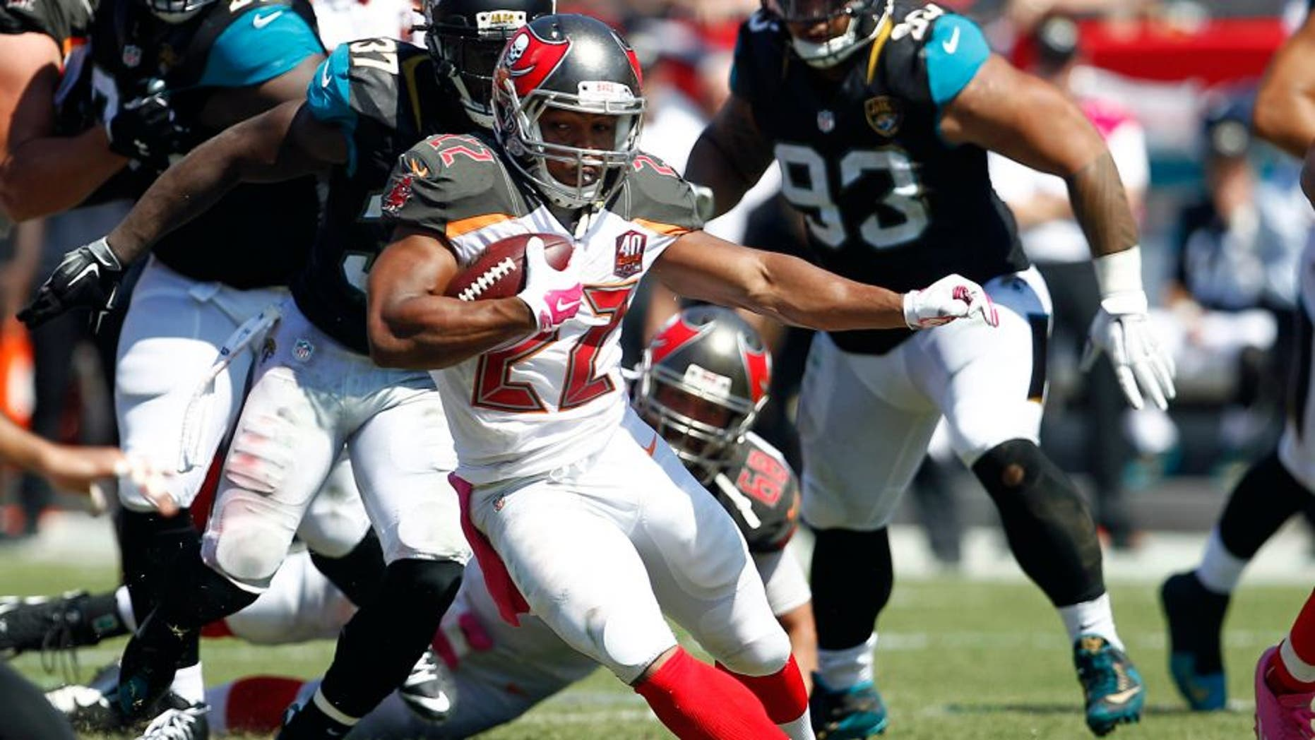 Oct 11, 2015; Tampa, FL, USA; Tampa Bay Buccaneers running back Doug Martin (22) runs for a first down during past Jacksonville Jaguars strong safety Johnathan Cyprien (37) the second quarter of an NFL football game at Raymond James Stadium. Mandatory Credit: Reinhold Matay-USA TODAY Sports
