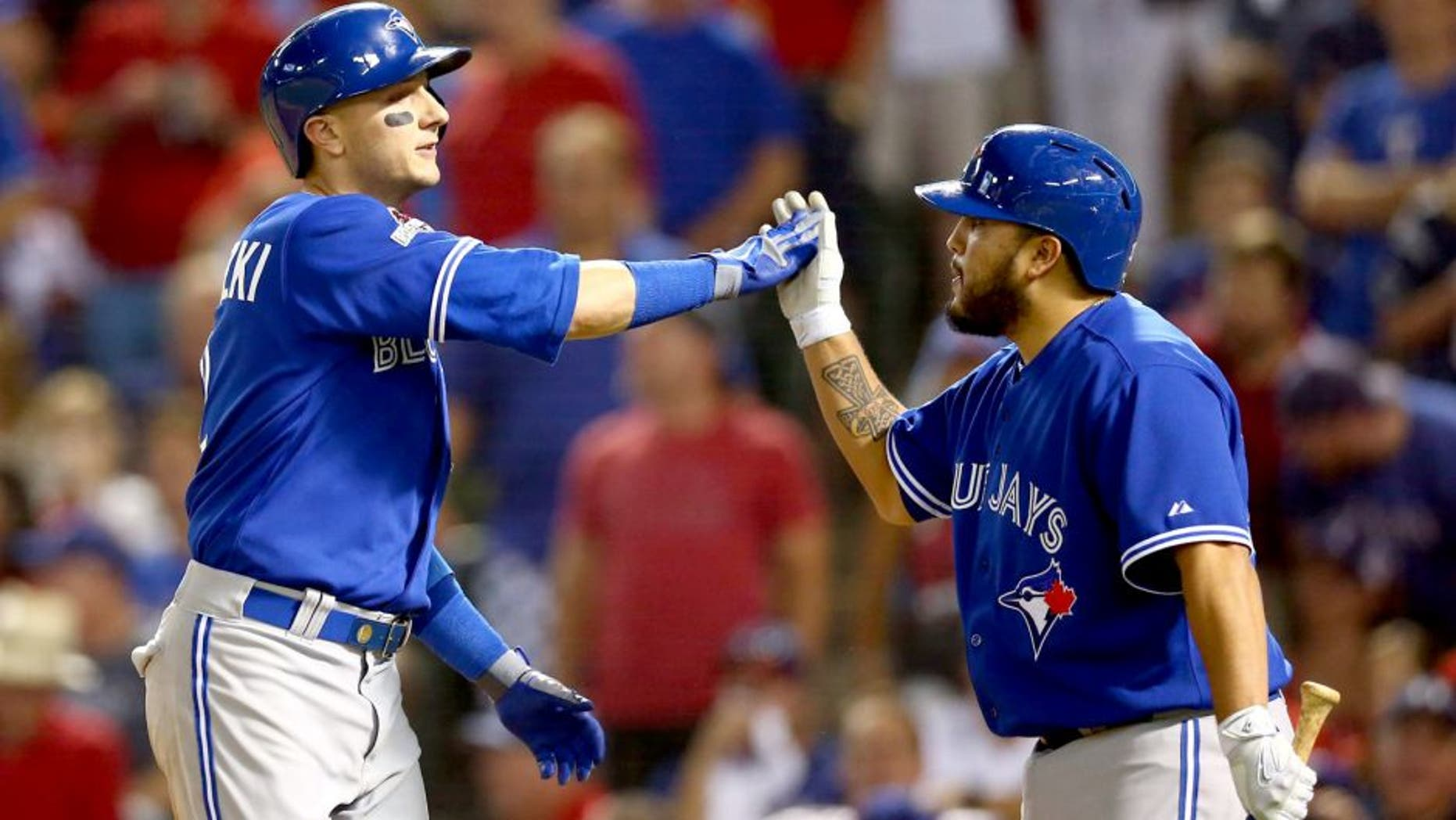 ARLINGTON, TX - OCTOBER 11: Troy Tulowitzki #2 of the Toronto Blue Jays celebrates with his teammate Dioner Navarro #30 after hitting a three run home run against Chi Chi Gonzalez #21 of the Texas Rangers in the sixth inning during game three of the American League Division Series on October 11, 2015 in Arlington, Texas. (Photo by Ronald Martinez/Getty Images)