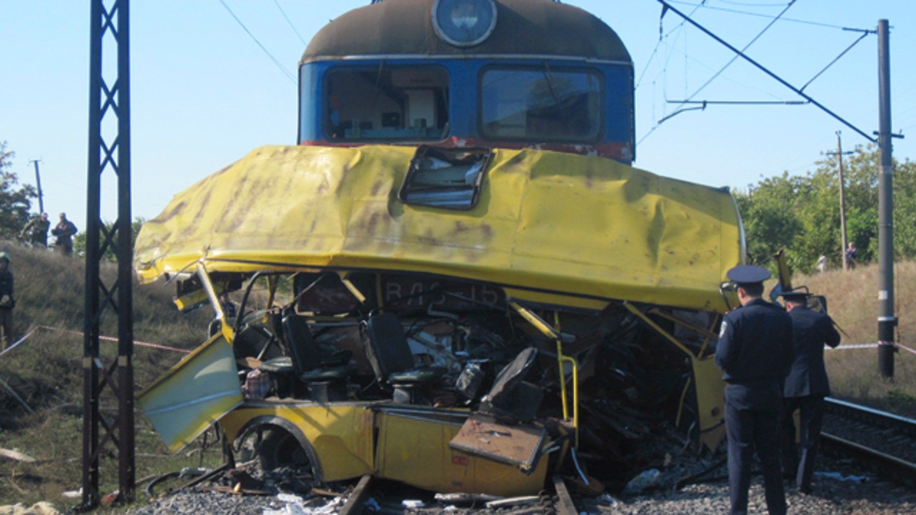 The remains of a bus lay next to a railway train at the site of an accident outside the town of Marhanets, Ukraine, Tuesday, Oct. 12, 2010. The crowded passenger bus collided with a train in eastern Ukraine Tuesday, killing 40 people and leaving 11 in critical condition, police said.