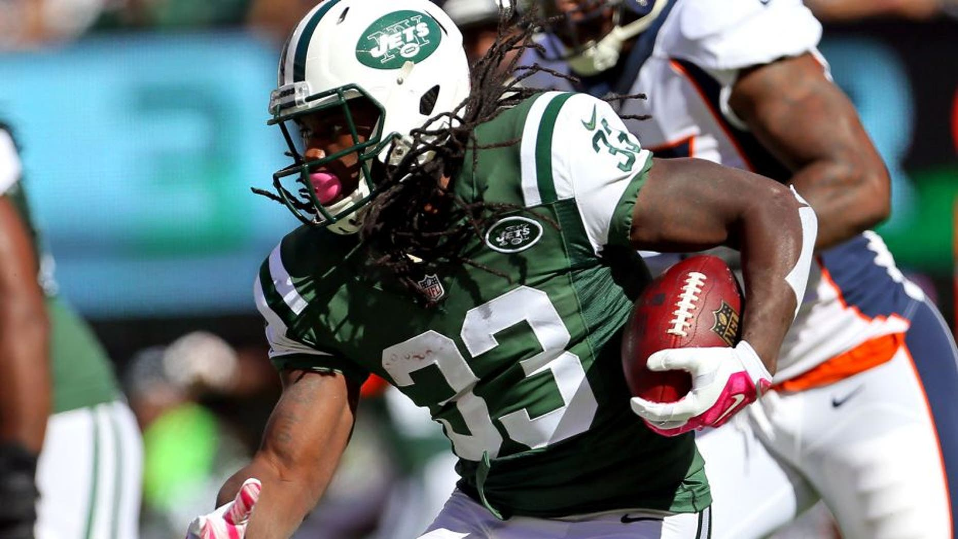 Oct 12, 2014; East Rutherford, NJ, USA; New York Jets running back Chris Ivory (33) rushes against the Denver Broncos during the first quarter of their NFL football game at MetLife Stadium. Mandatory Credit: Adam Hunger-USA TODAY Sports