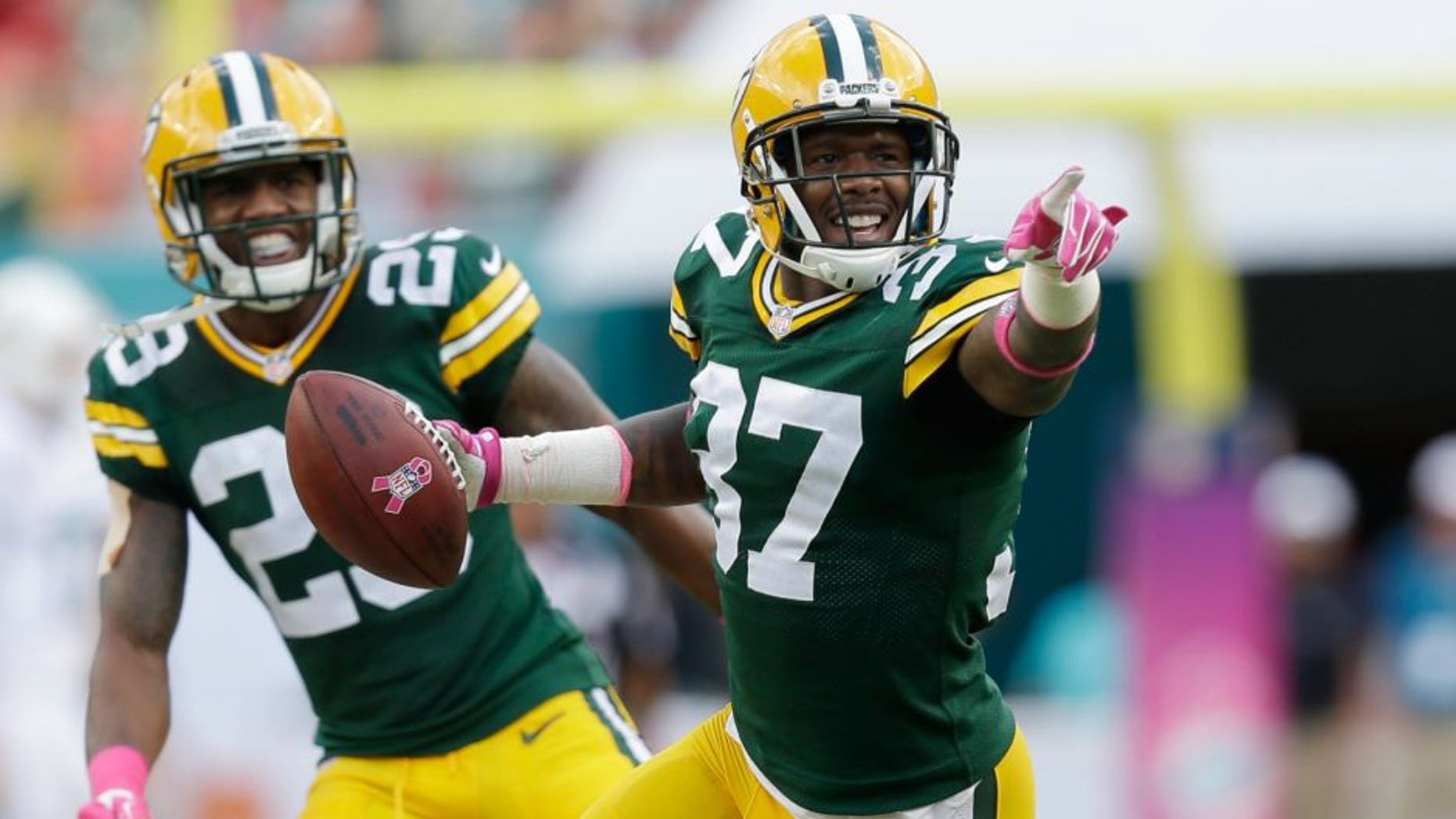 Green Bay Packers cornerback Sam Shields (37) points to the sidelines after intercepting a ball intended for Miami Dolphins wide receiver Brian Hartline (82) during the first half of an NFL football game, Sunday, Oct. 12, 2014, in Miami Gardens, Fla. In the background is Green Bay Packers cornerback Casey Hayward (29). (AP Photo/Wilfredo Lee)